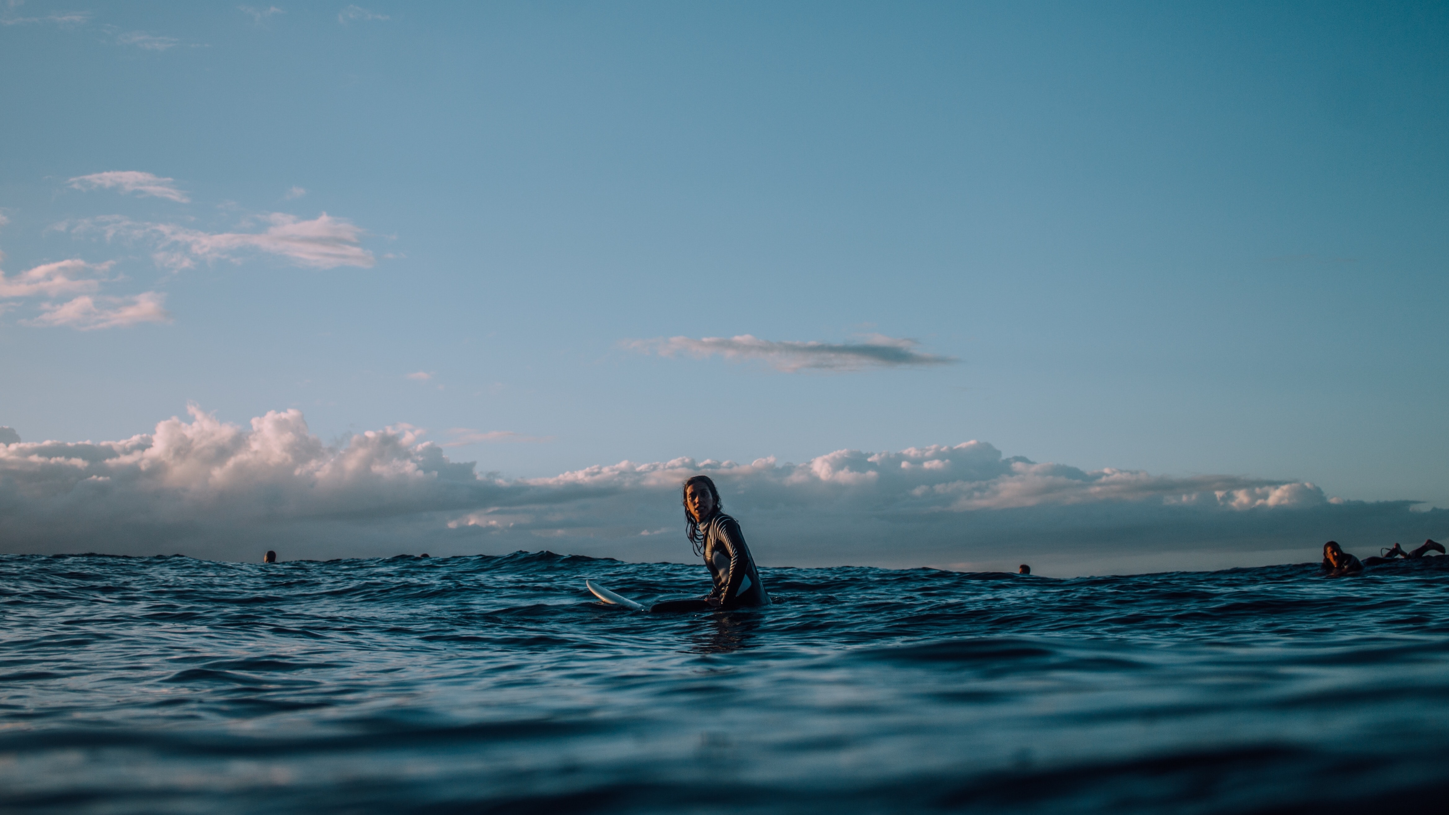 person sitting on surfboard surrounded by blue ocean during daytime