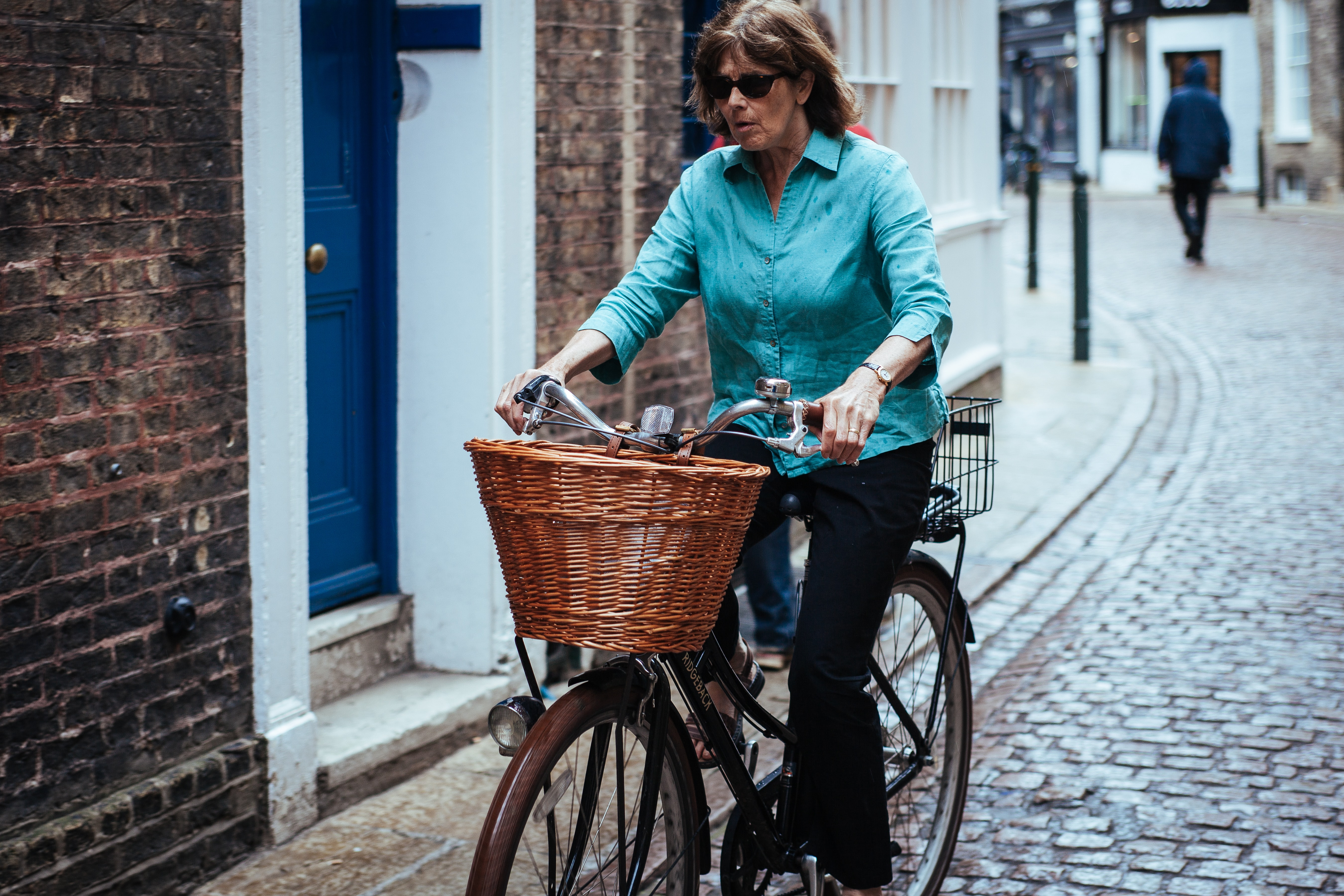A middle-aged woman in a blue shirt riding a bicycle on a cobbled street