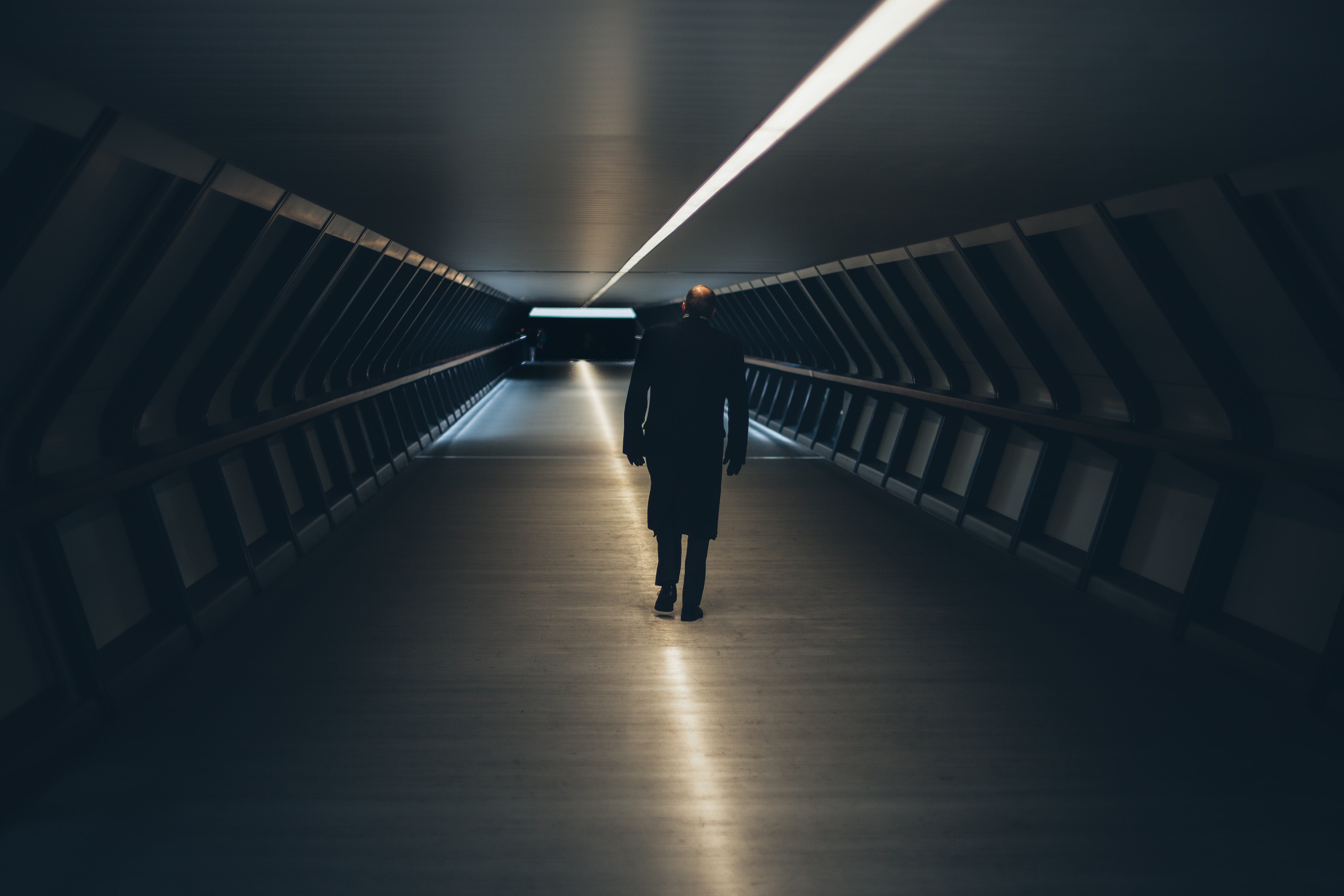 person wearing black long-sleeved shirt walking on tunnel
