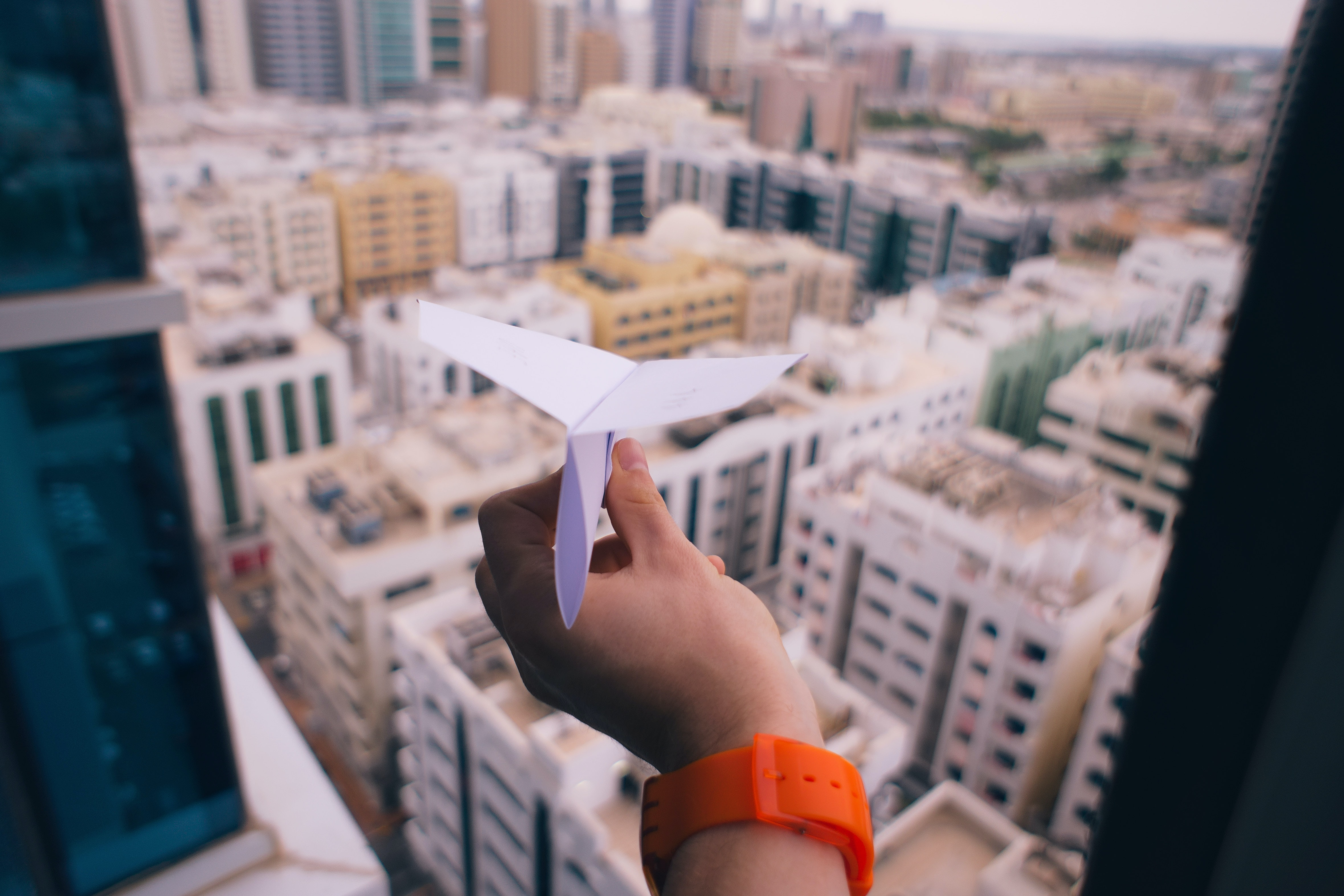 A person holding a paper airplane out a window in Abu Dhabi