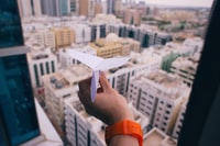 shallow focus photography of person holding paper plane