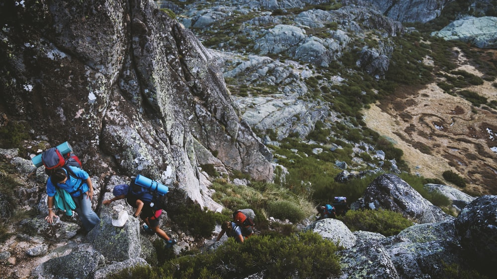 several mountain climbers on cliff of rock mountain at daytime