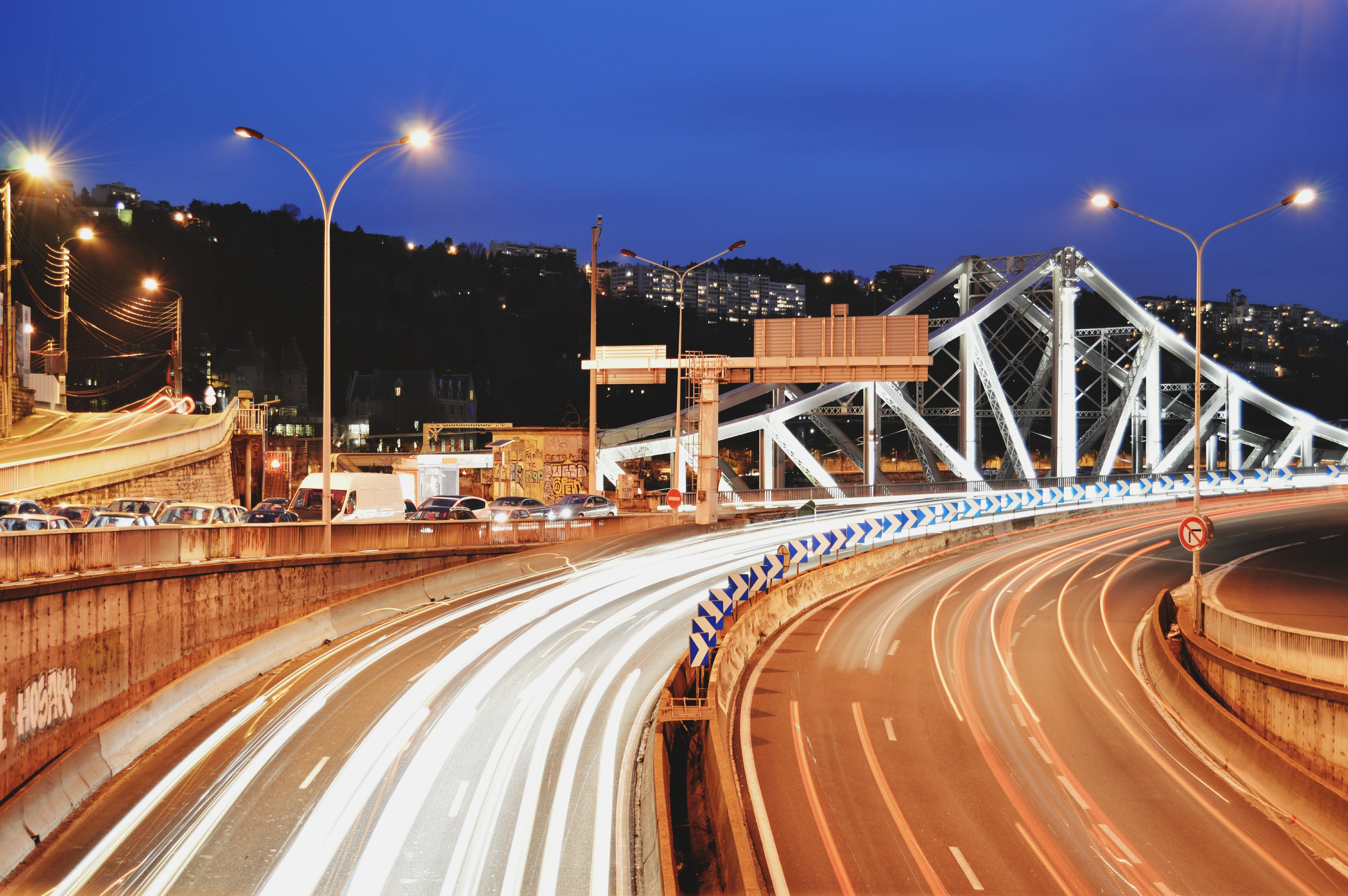 A time lapsed photo making car lights travel at high speed near a bridge on Autoroute A7