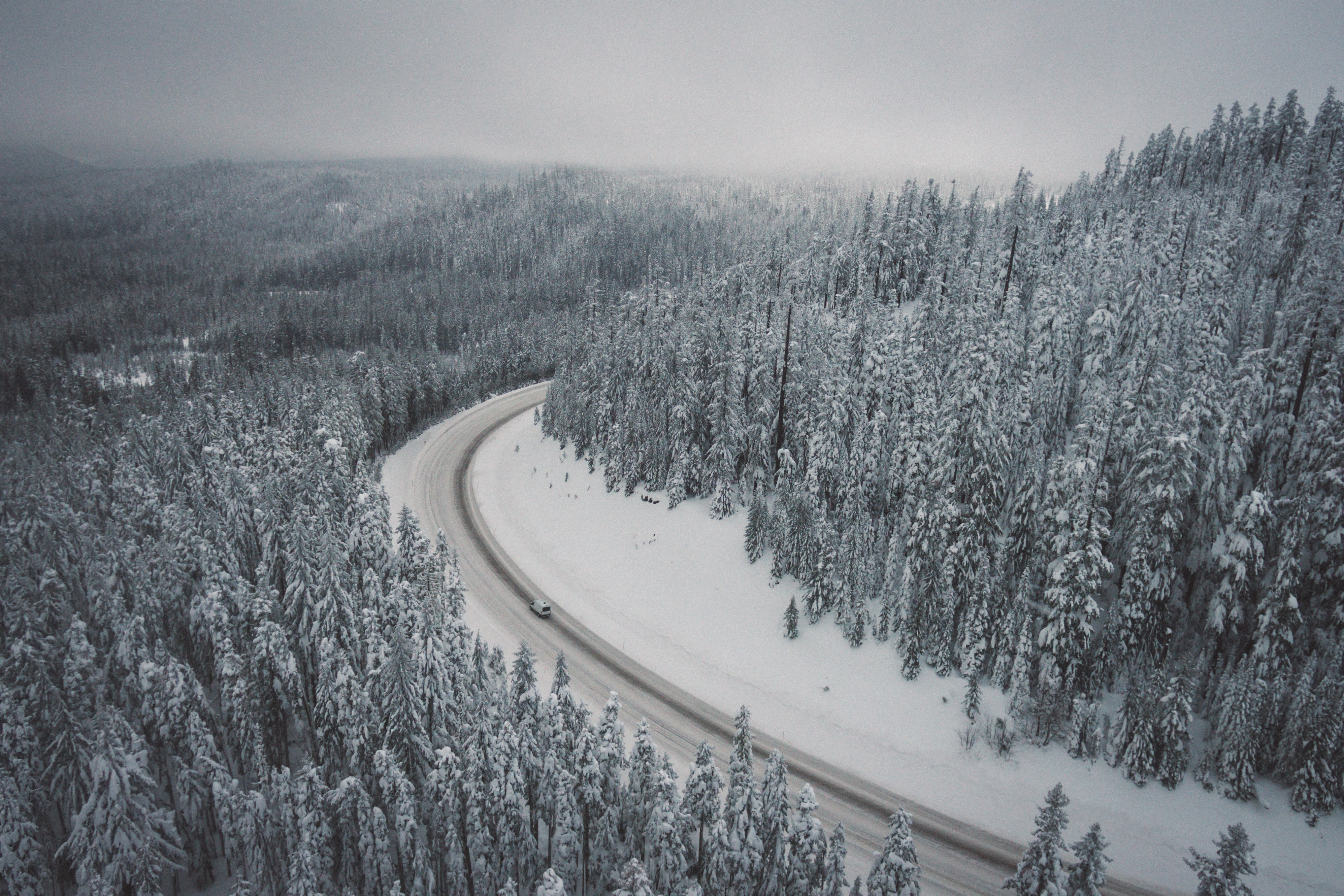 Winding winter road through a snowy forest landscape