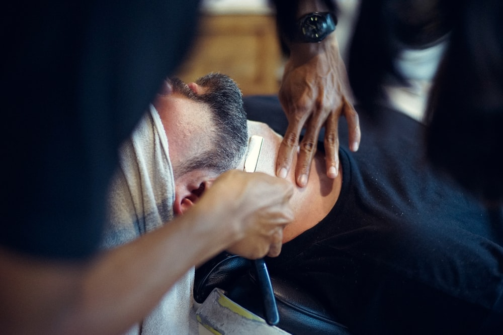 Person getting their beard groomed.