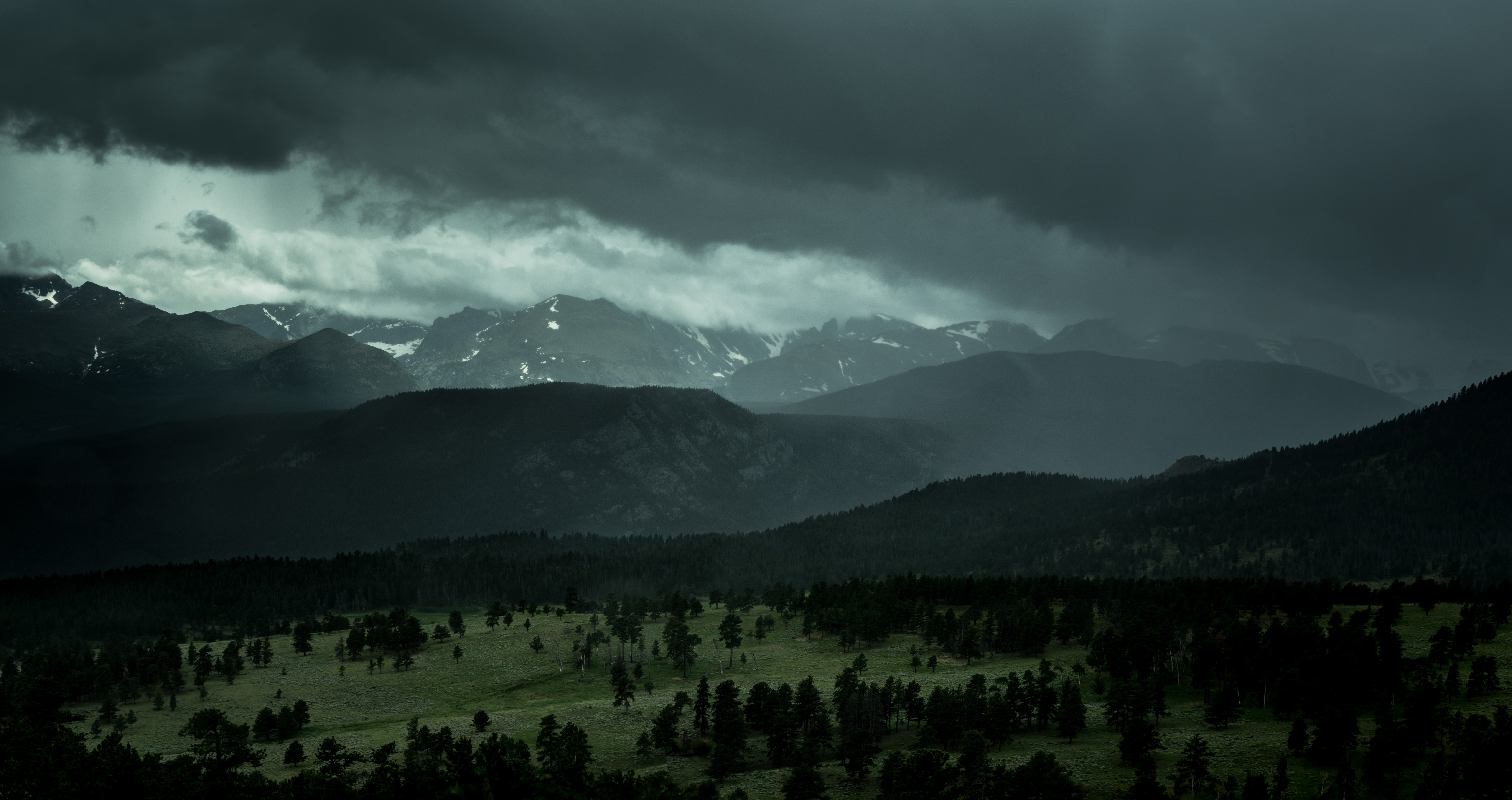 Overcast sky over a wooded plain near the mountains in Rocky Mountain National Park