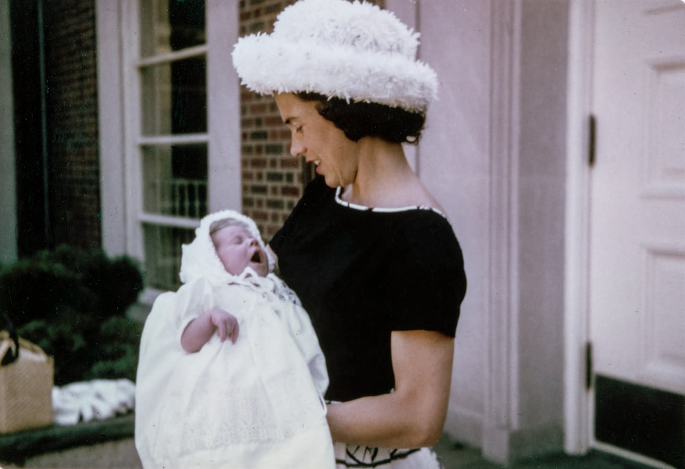 woman carrying baby standing near white wooden door