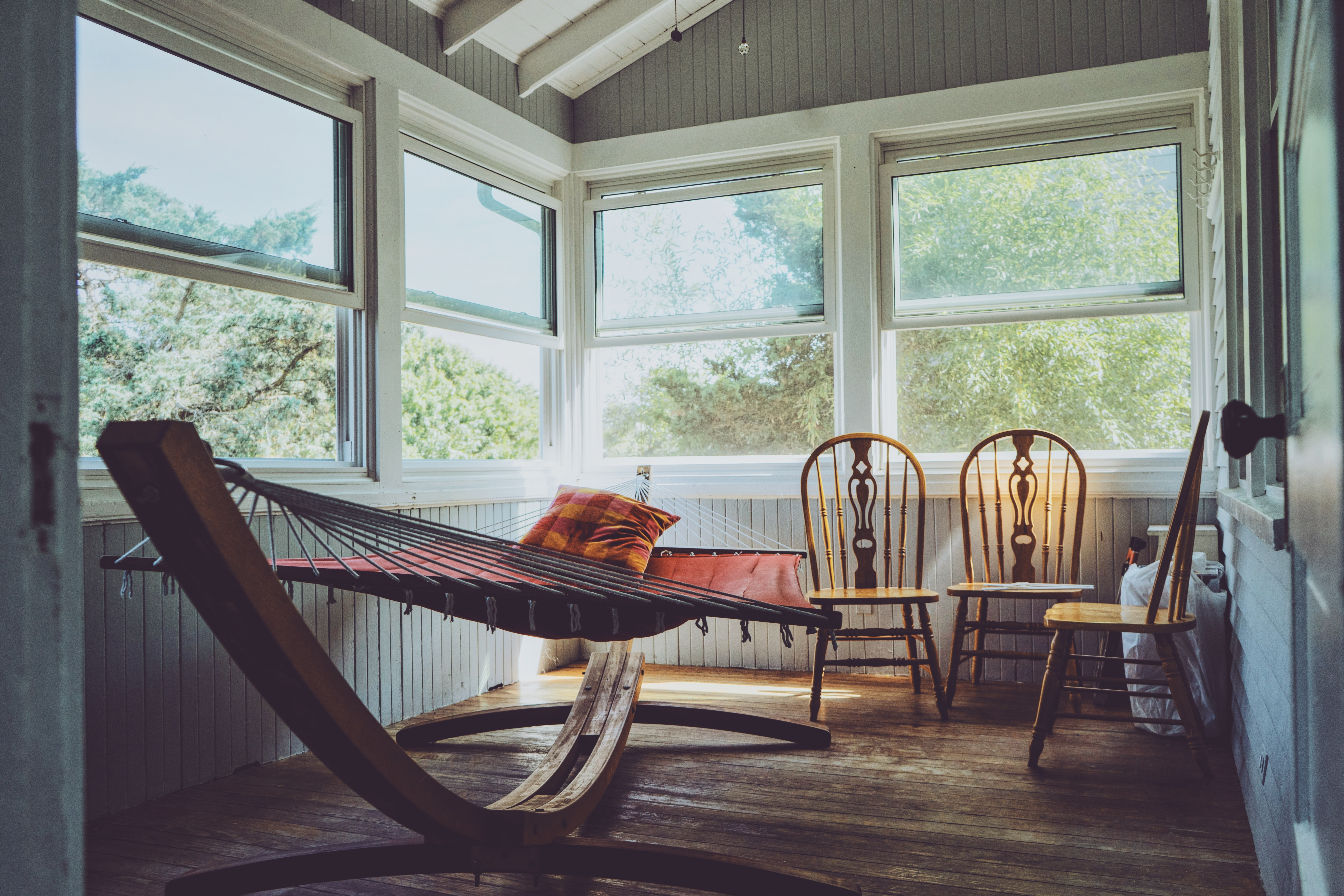 photography of grey, white, and brown wooden house interior with three brown wooden Windsor chairs beside brown hammock with glass windows