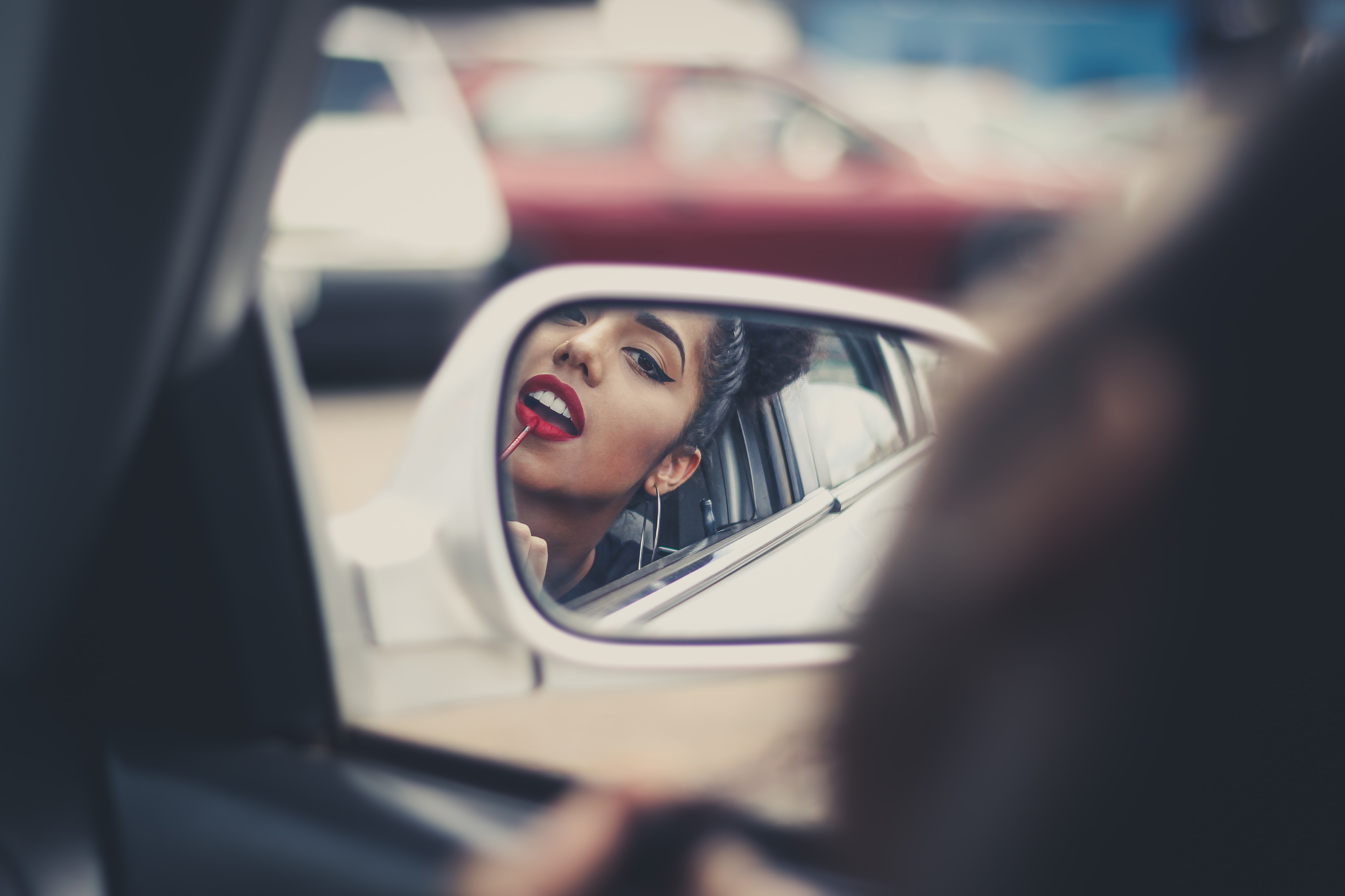 woman putting liquid lipstick on her lips while looking at vehicle's mirror during daytime