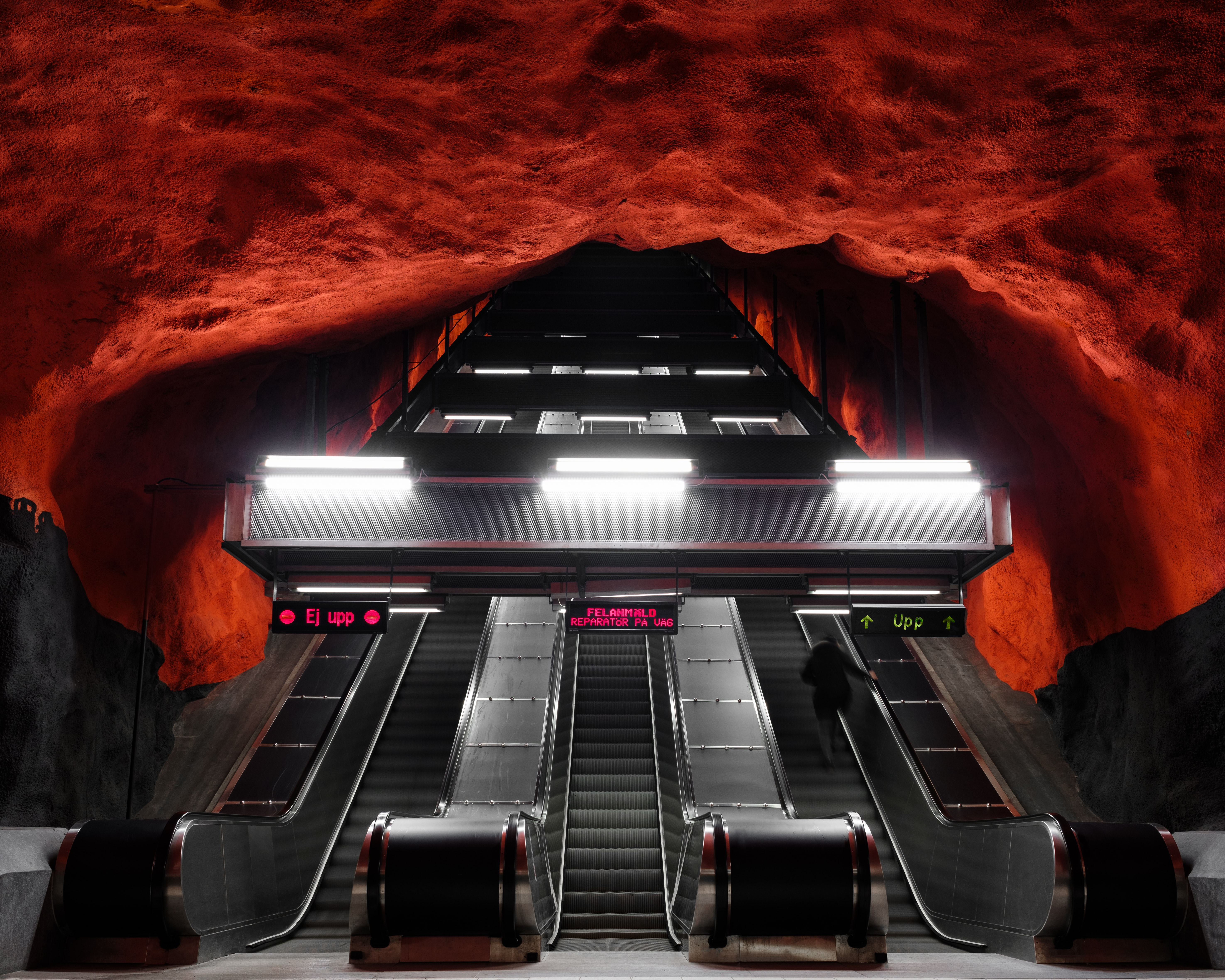 Bottom view of escalator in underground metro station underneath red rock ceiling