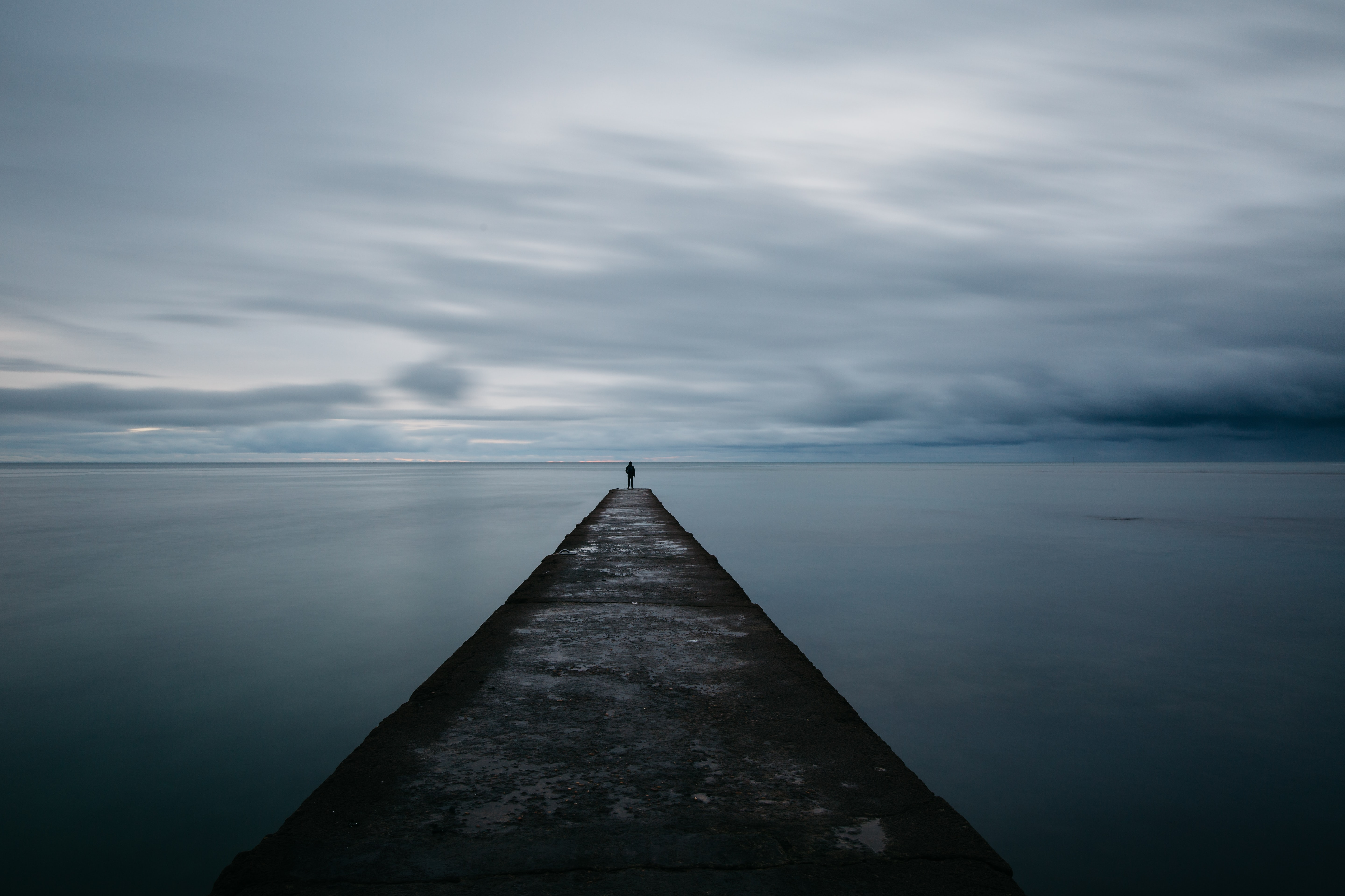 A silhouette of a person at the edge of a long pier