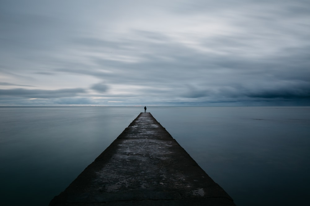 person standing on grey concrete pier under cloudy sky