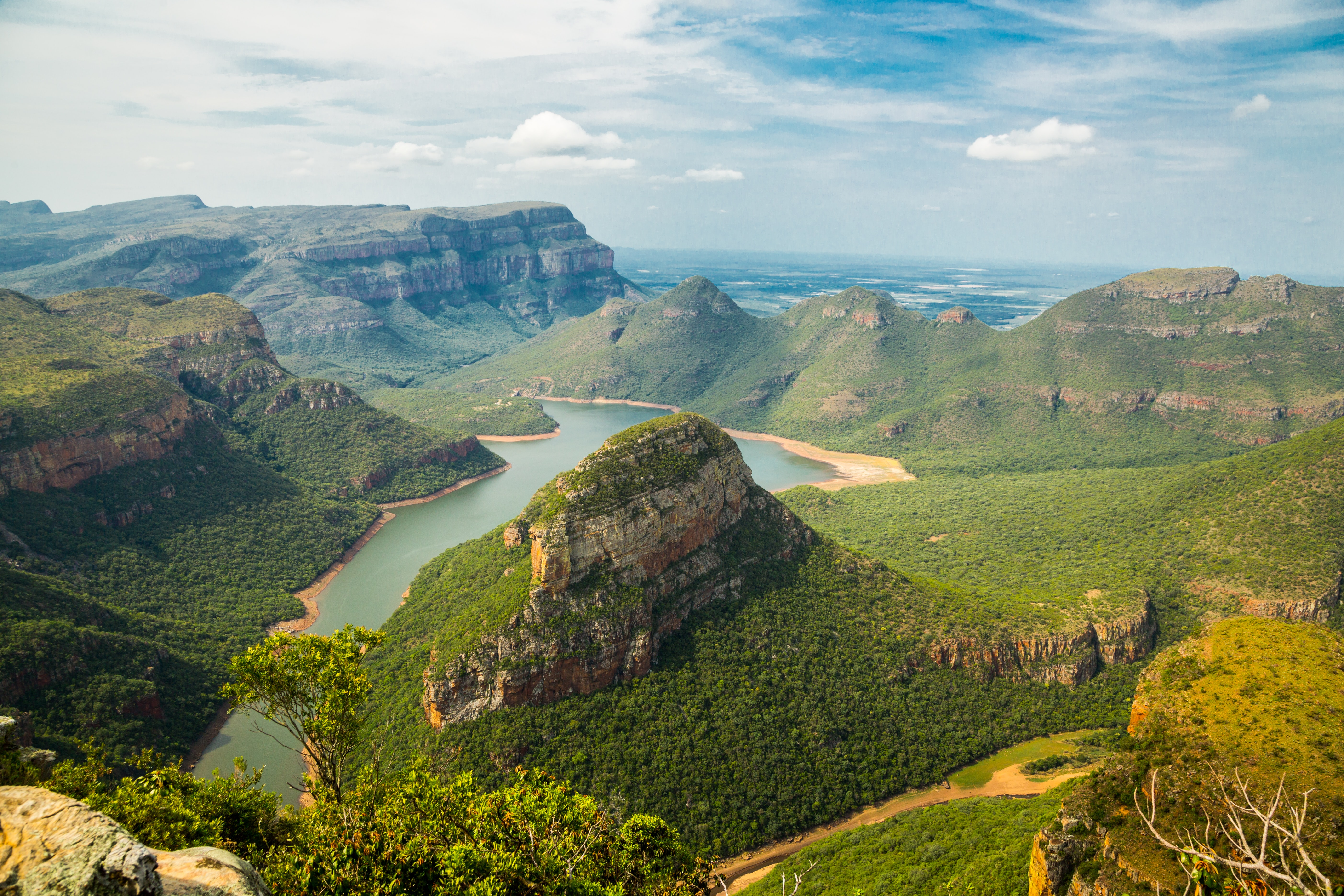 A high view of a lush mountain valley with a lake in South Africa