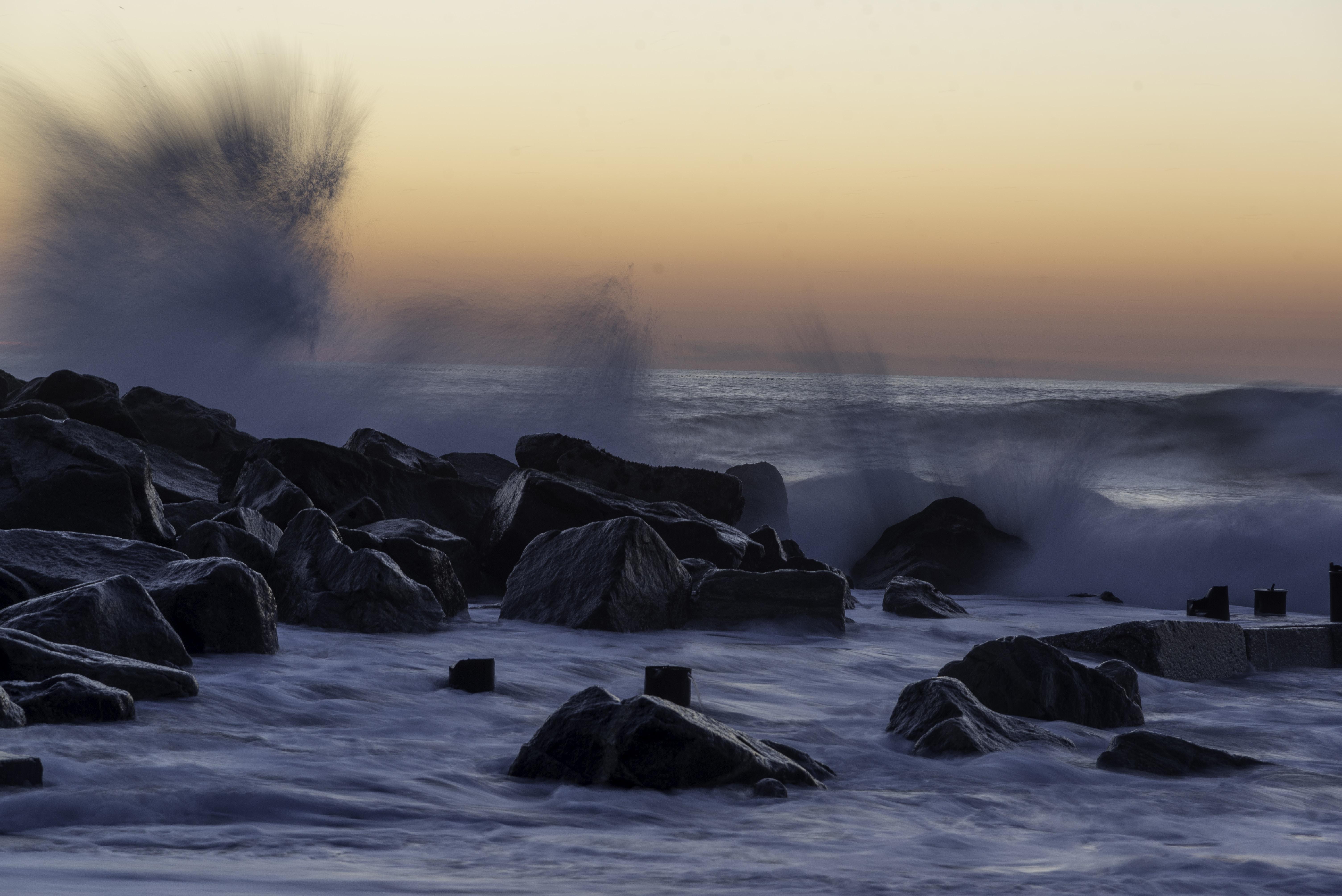 black rocks of splashing body of water
