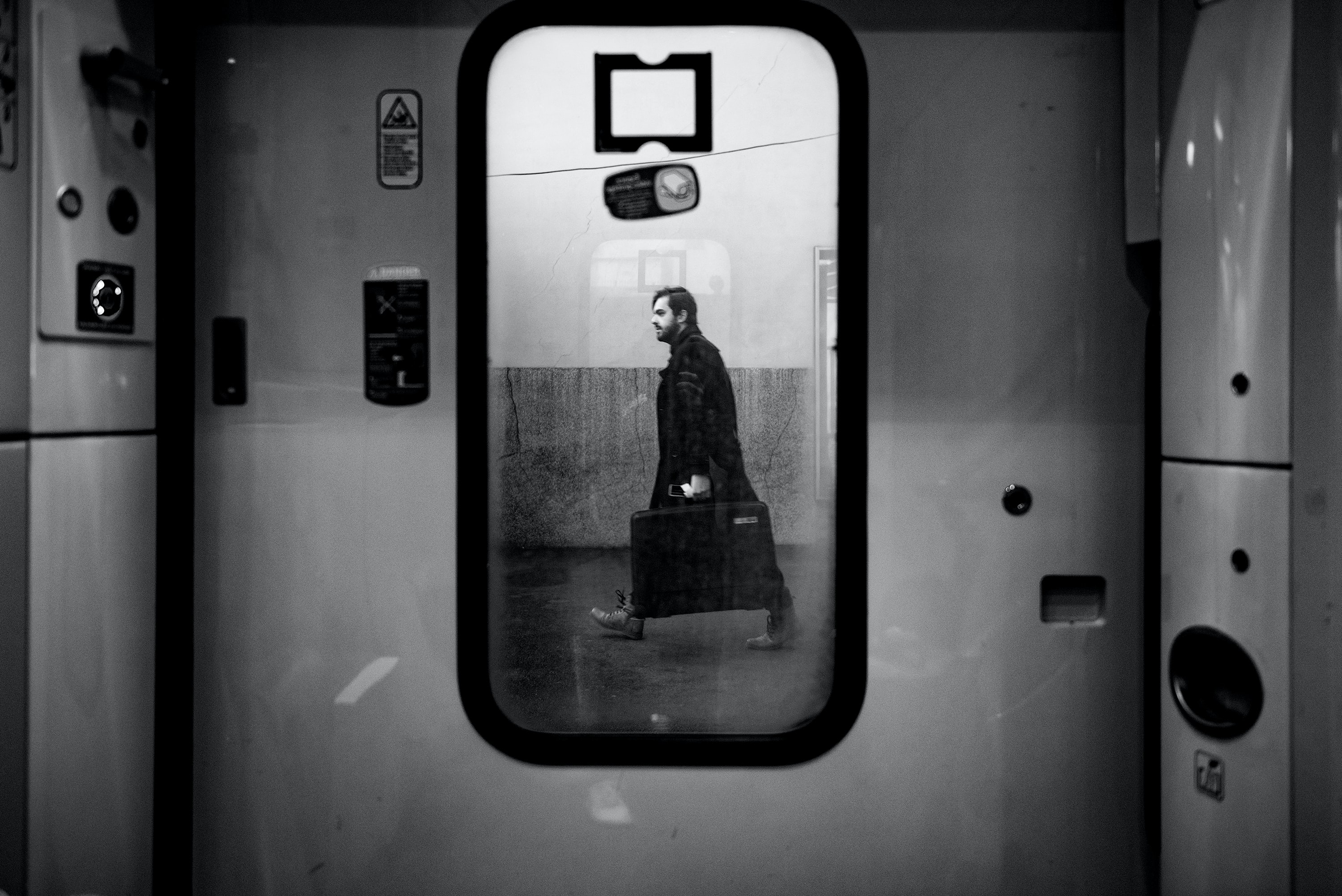 Black and white shot through train door window of male commuter walking on platform, Le Havre