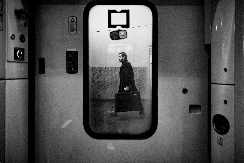 man walking outside train door in grayscale photo