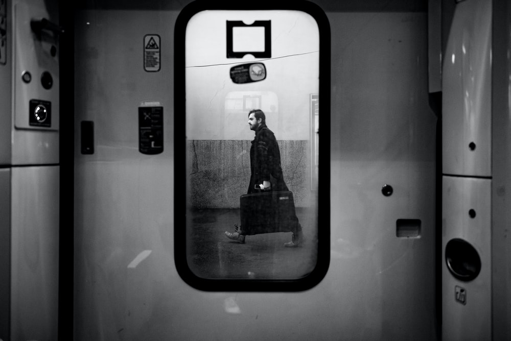 man walking outside train door in grayscale photo