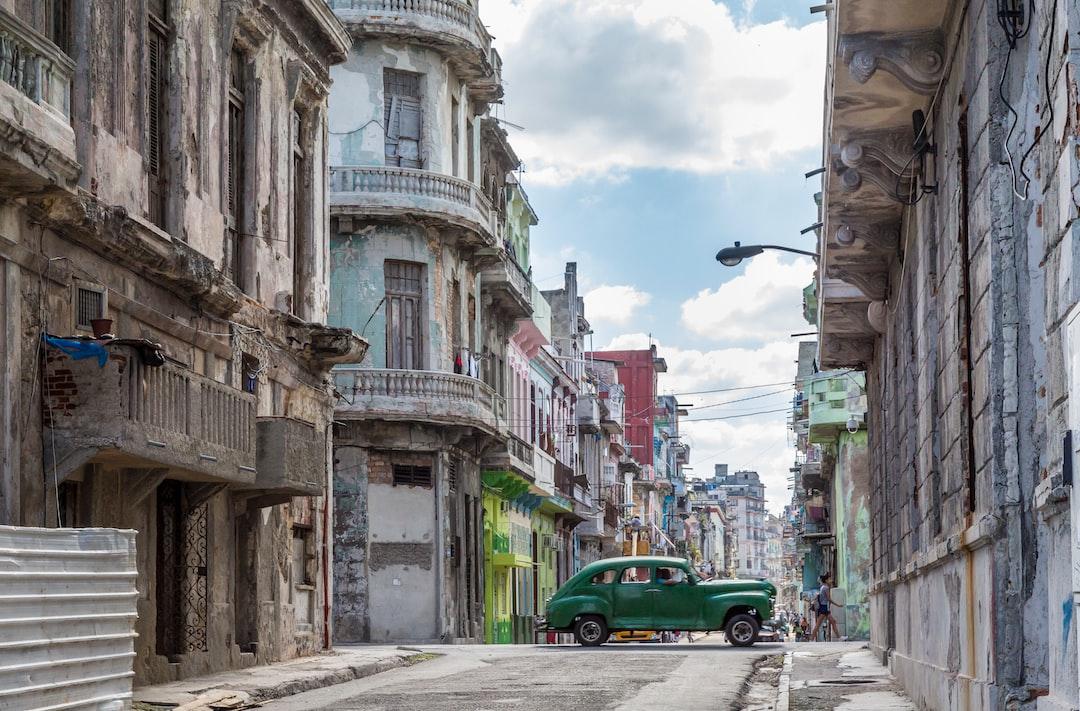 Auto antiguo verde entre los edificios despintados en la Habana Vieja
