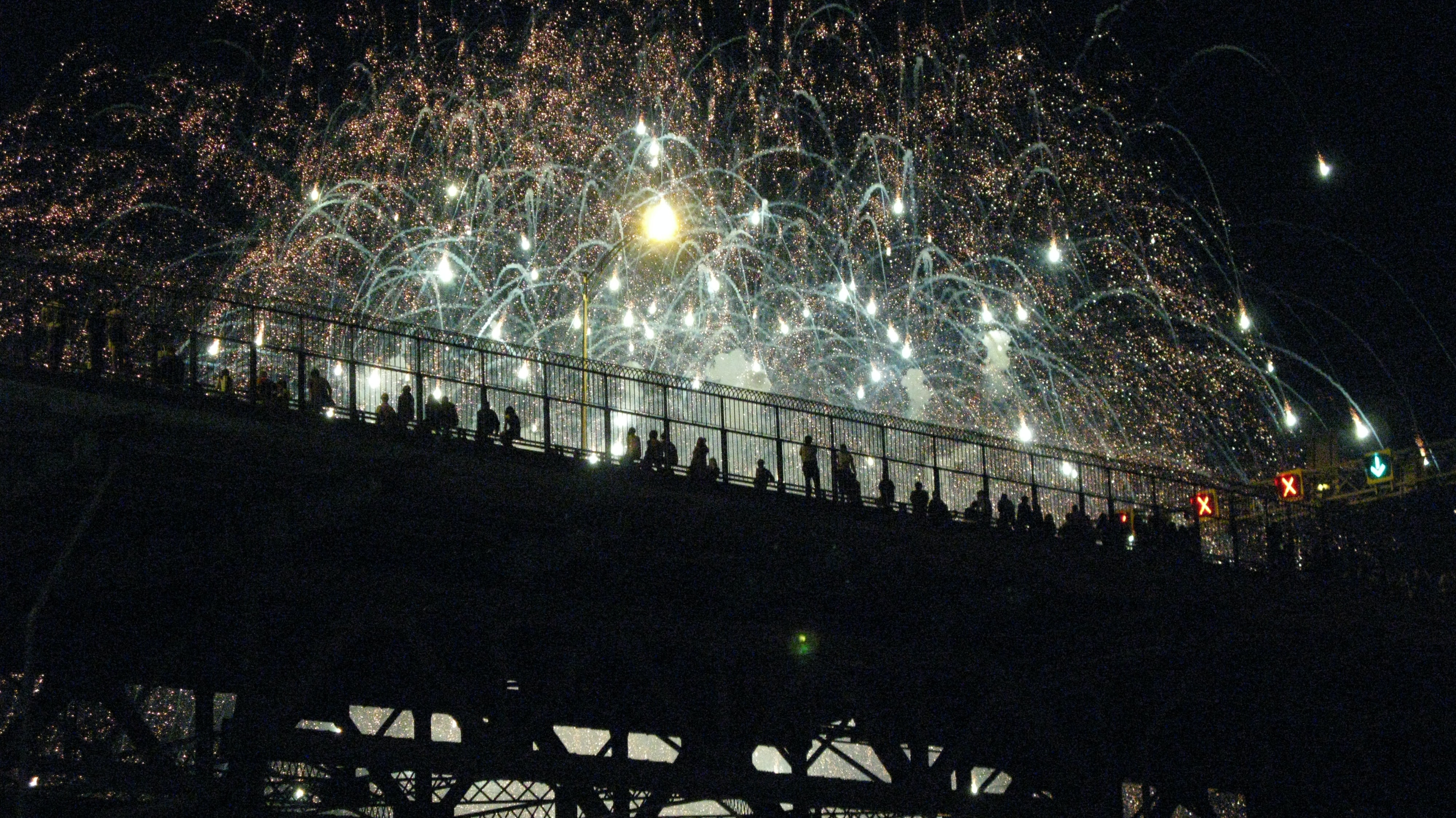 People on a bridge at night in Montreal celebrating with fireworks