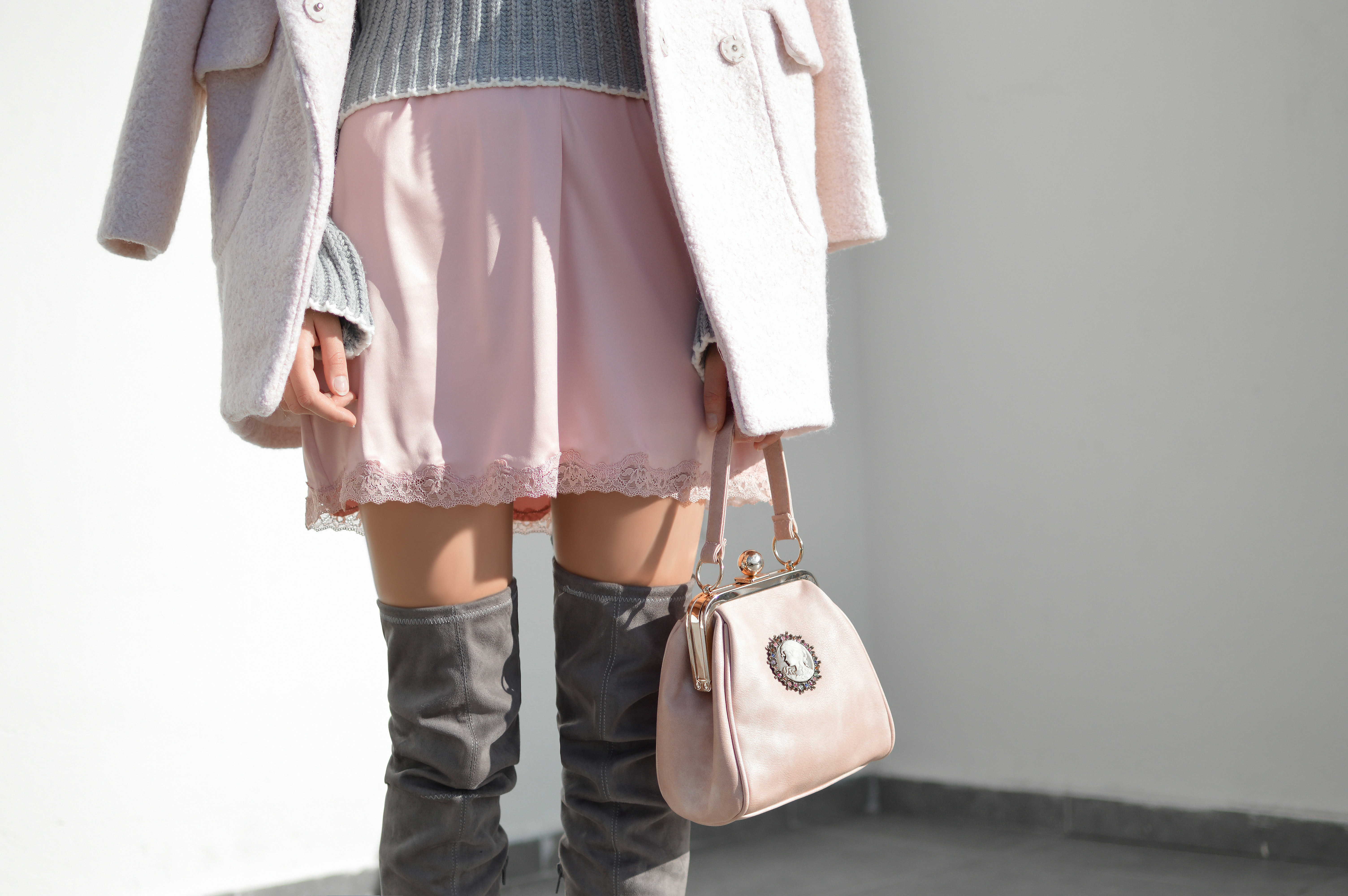 A woman in a pink skirt, long boots and a jacket carrying a pink handbag