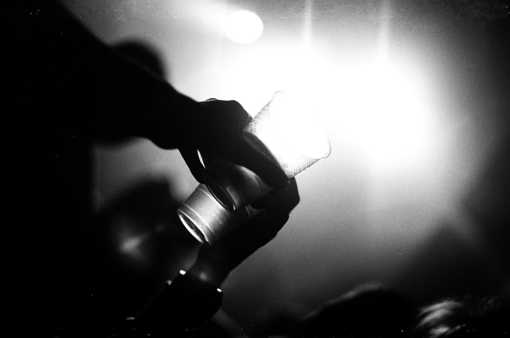 grayscale photography of person holding drinking glass