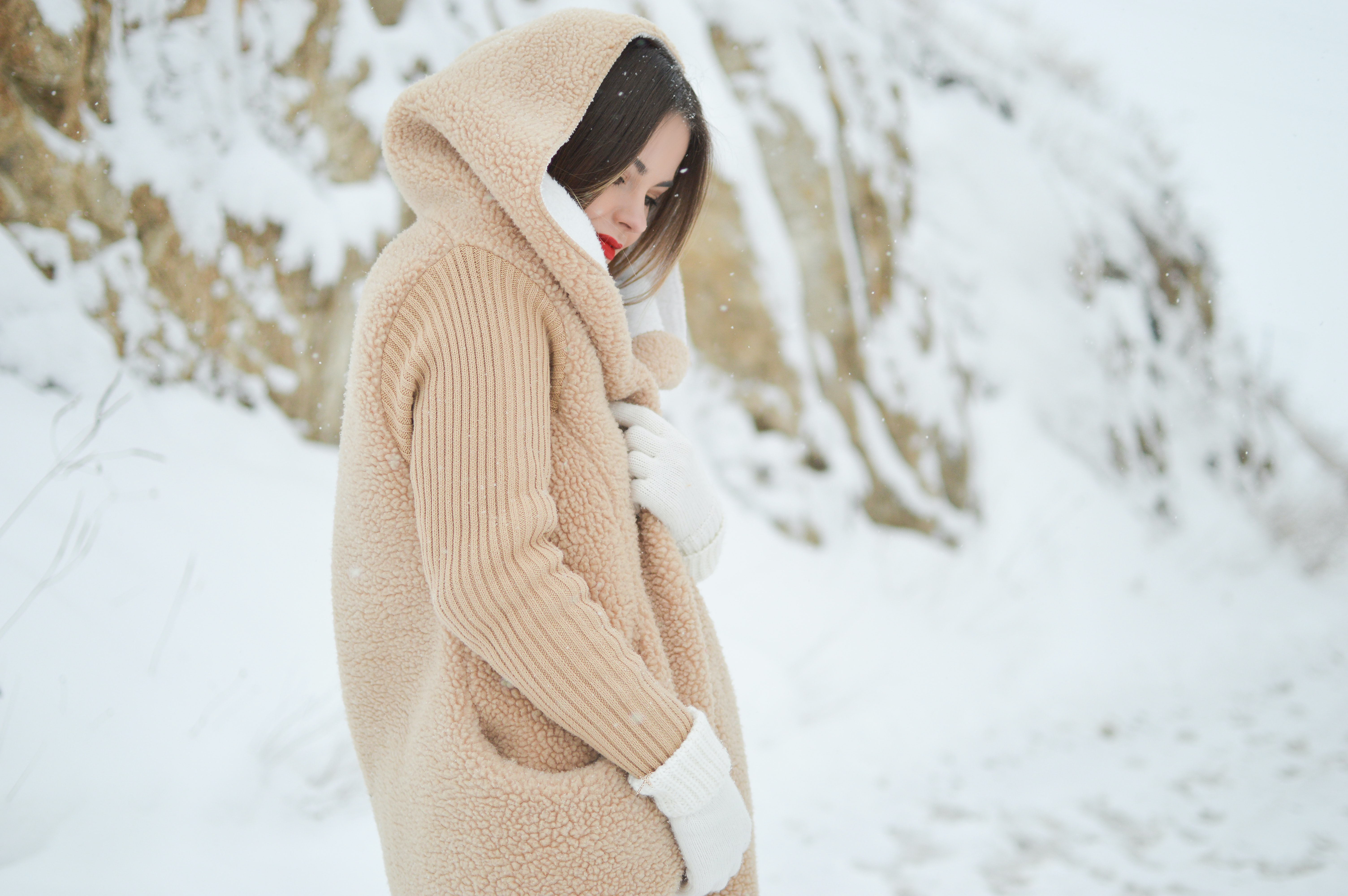 A woman in a furry hooded sweater wearing gloves in the snow in Florina