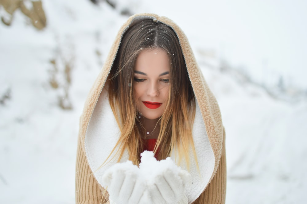 woman holding and looking at ice during daytime