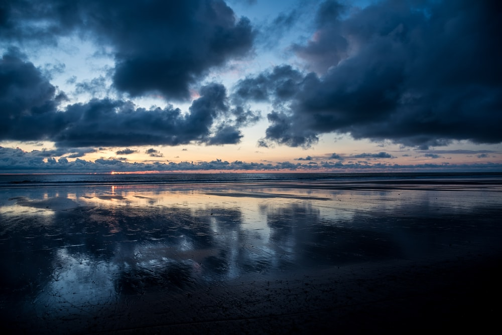 calm body of water under dark clouds