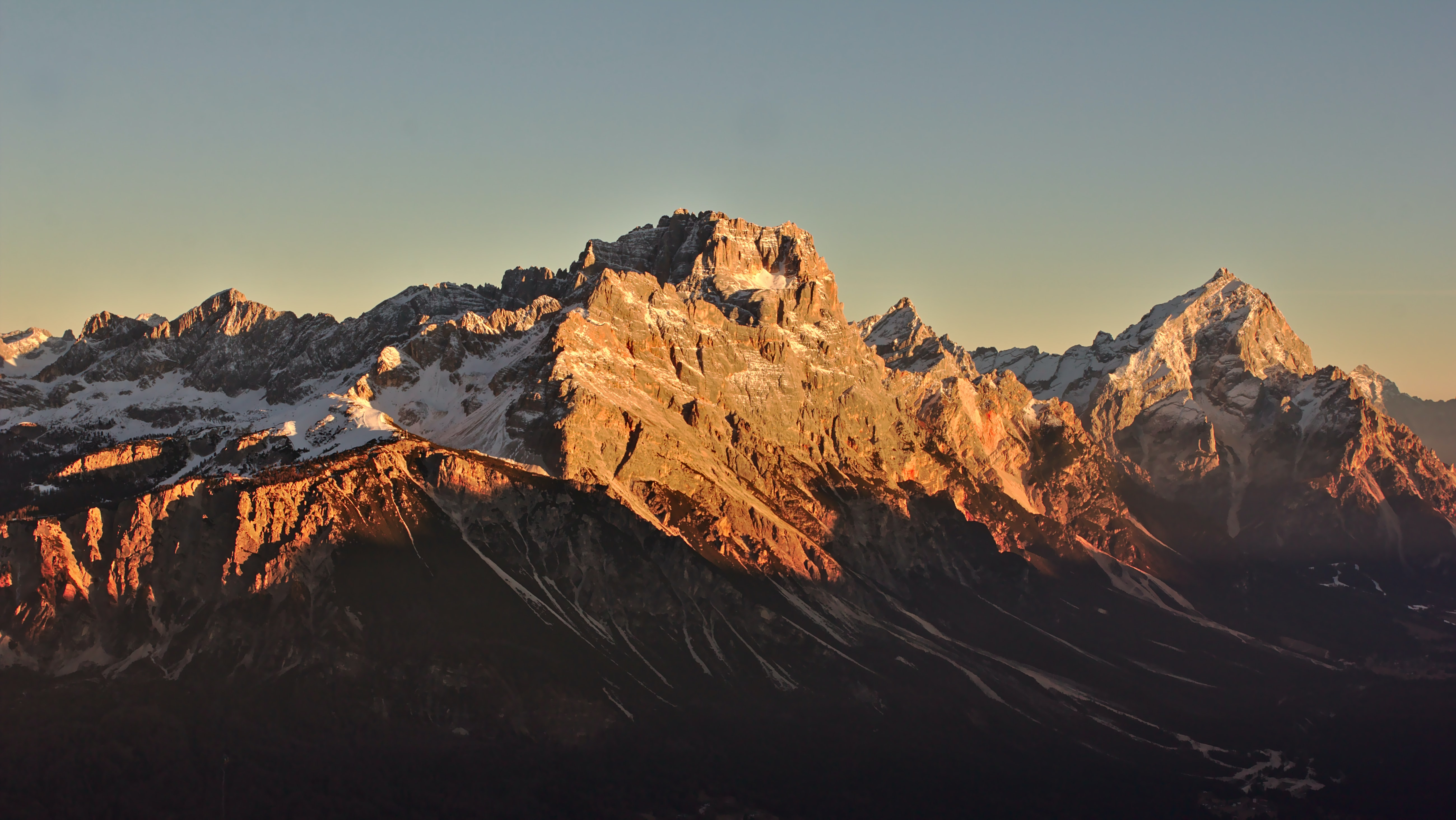 Tall mountain peaks and crests illuminated by the setting sun