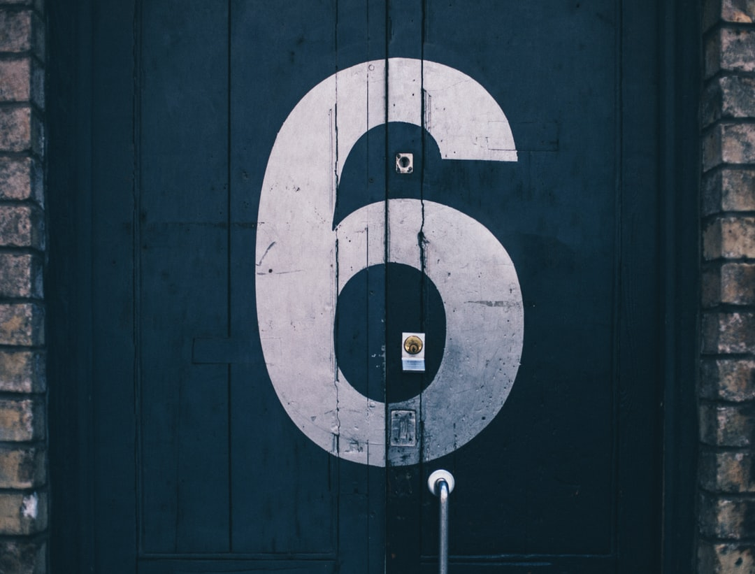 macro photography of blue wooden door painted with number 6