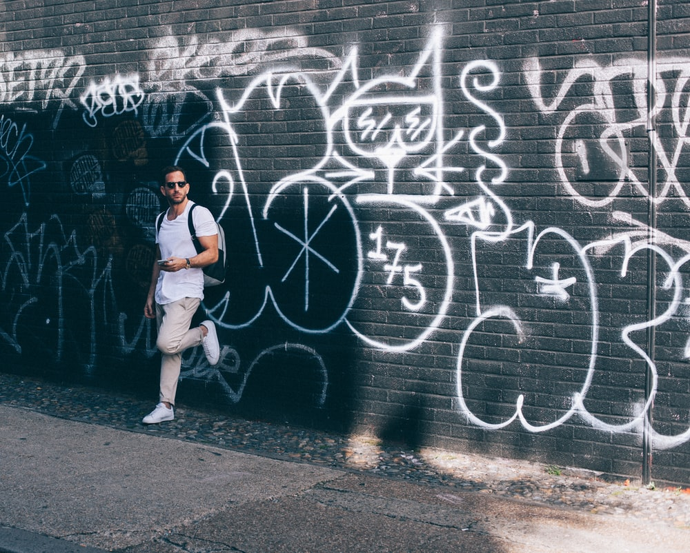man wearing white crew-neck T-shirt leaning on black wall with white graffiti