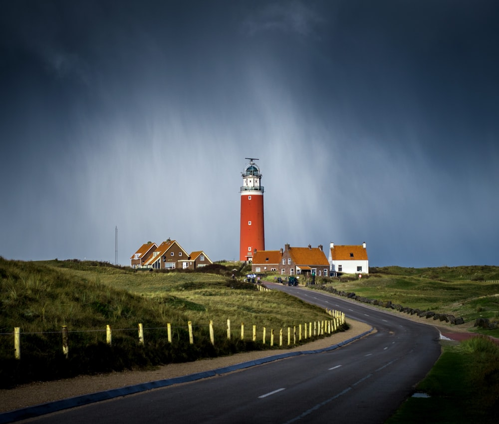 asphalt road between grass field going to brown lighthouse beside houses under cloudy sky