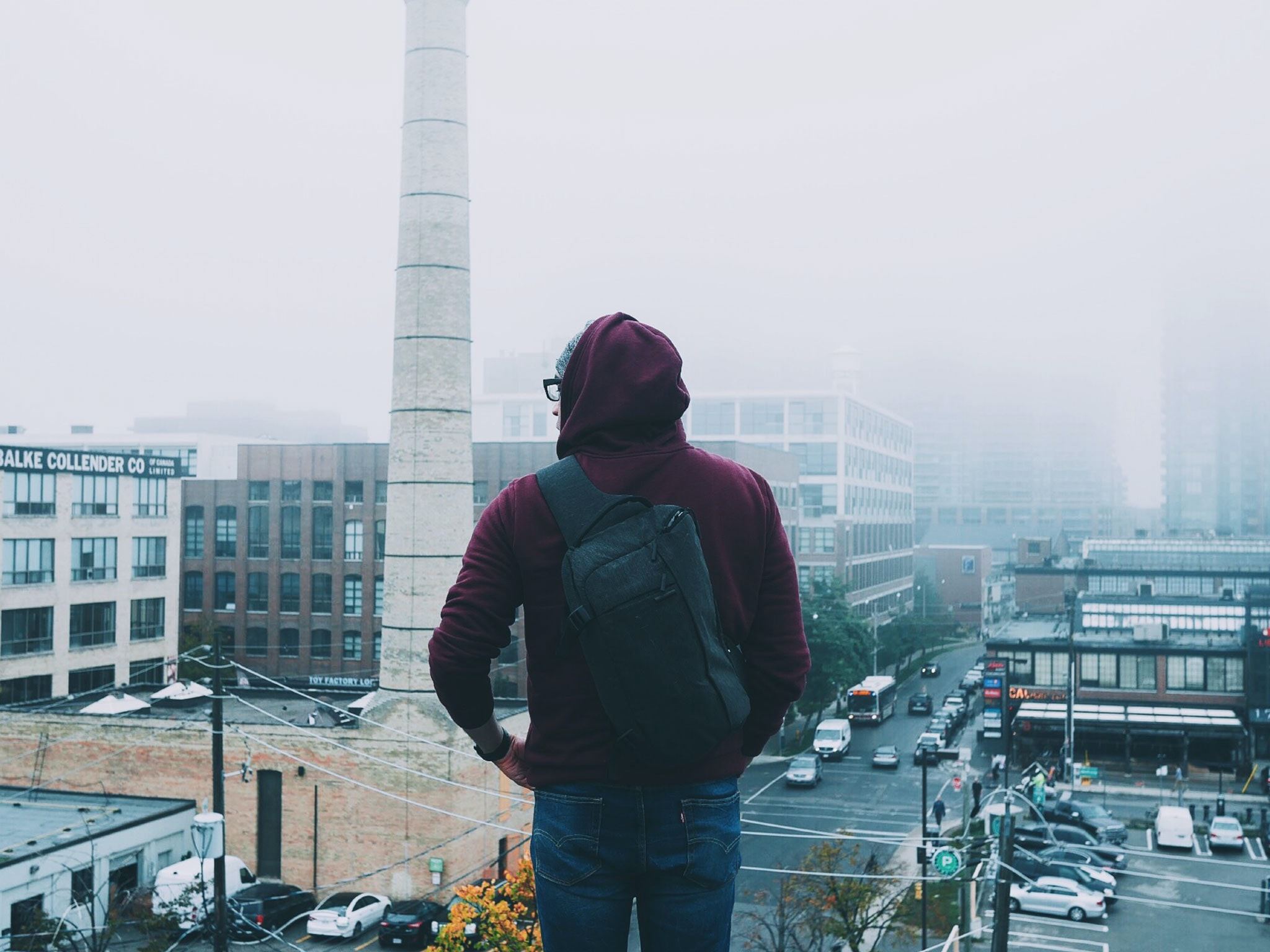 A hoodie wearing guy standing on top of a building and staring at the traffic throughout Liberty Village