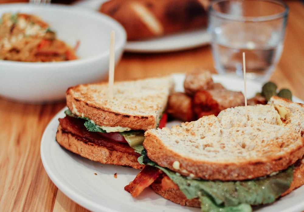two sliced of sandwich on plate near bowl and drinking glass