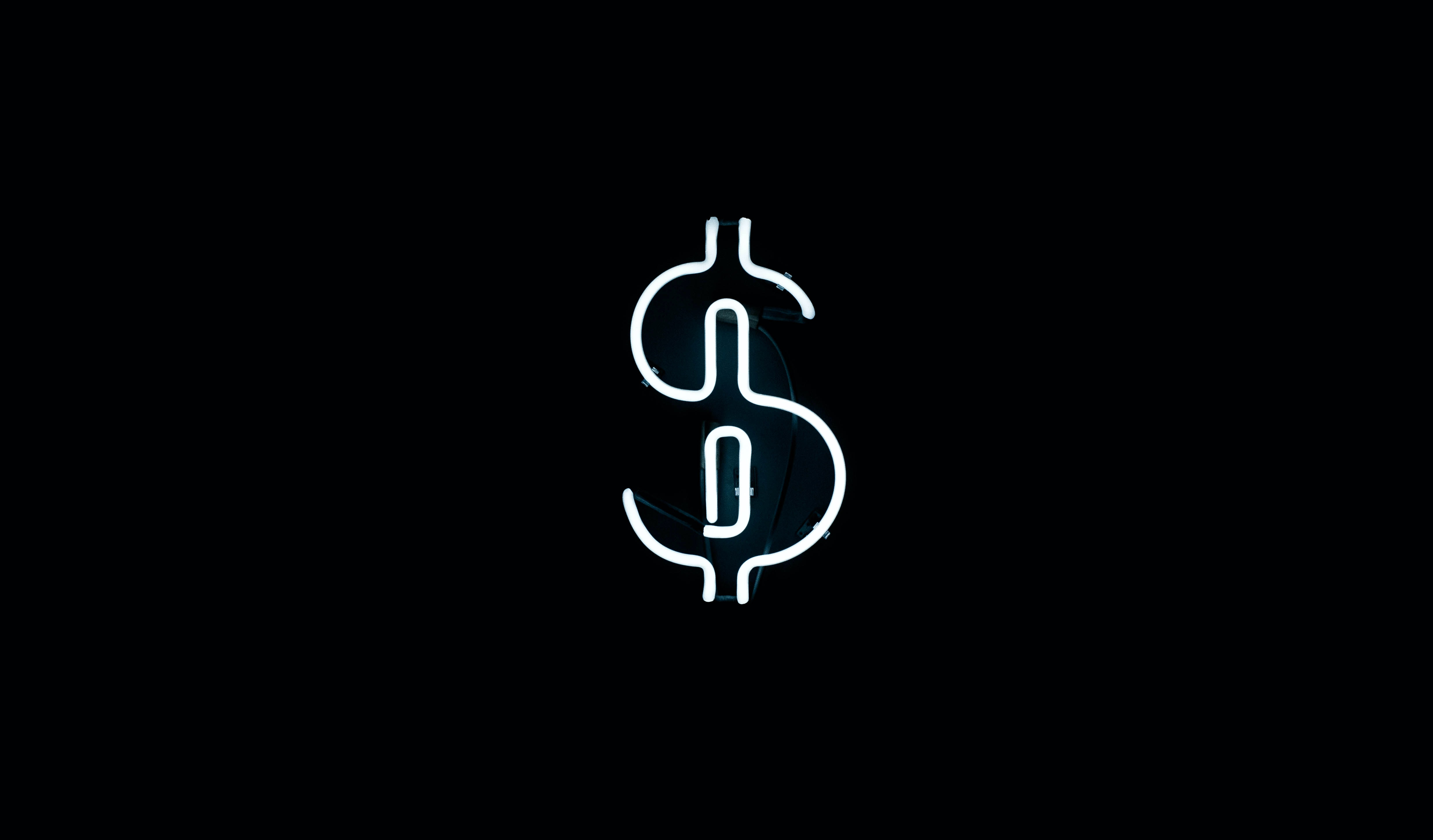 A white neon in the shape of the dollar sign at night