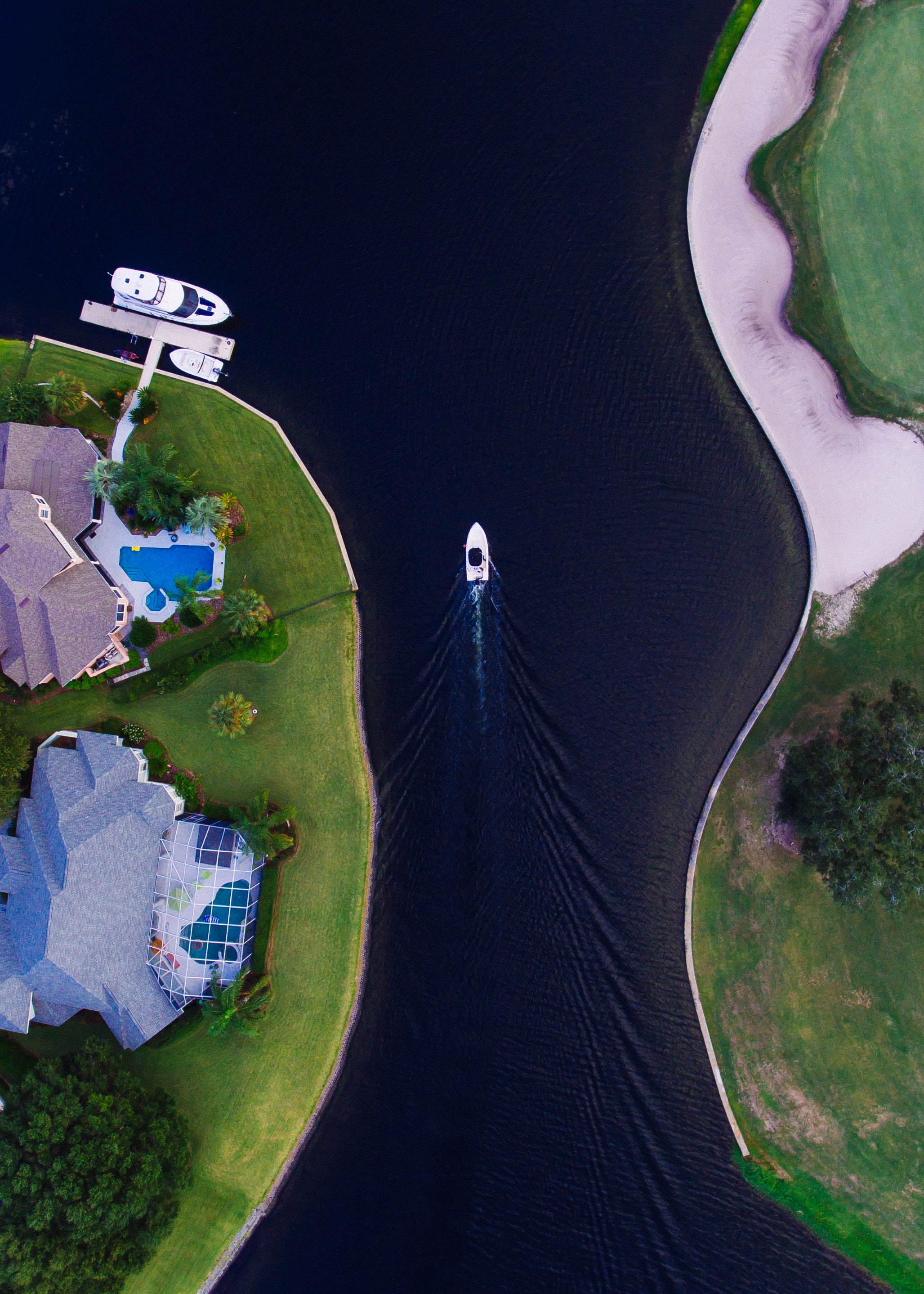 A drone view of a waterfront neighborhood of mansions and boats in Arlington, Jacksonville, Florida, United States