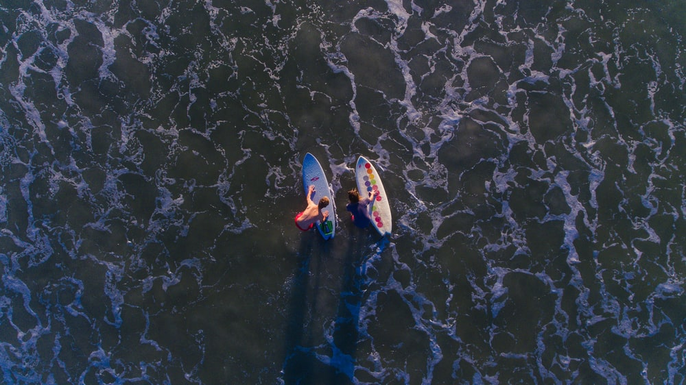 top view photo of two person with surfboards on water