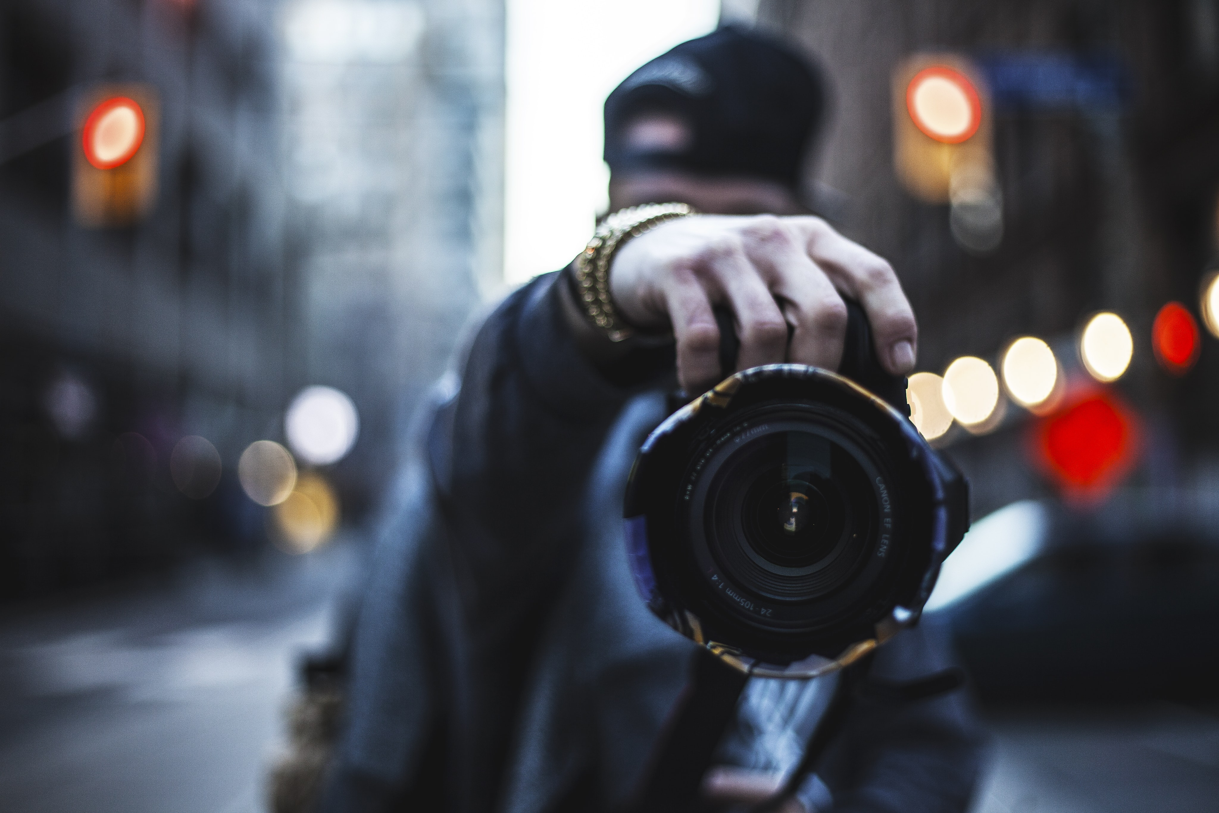 selective focus photography of man holding a camera at the street