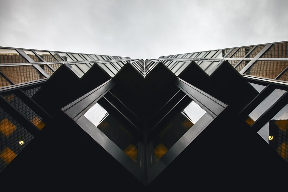lowangle photography of brown and black high-rise building under cloudy sky