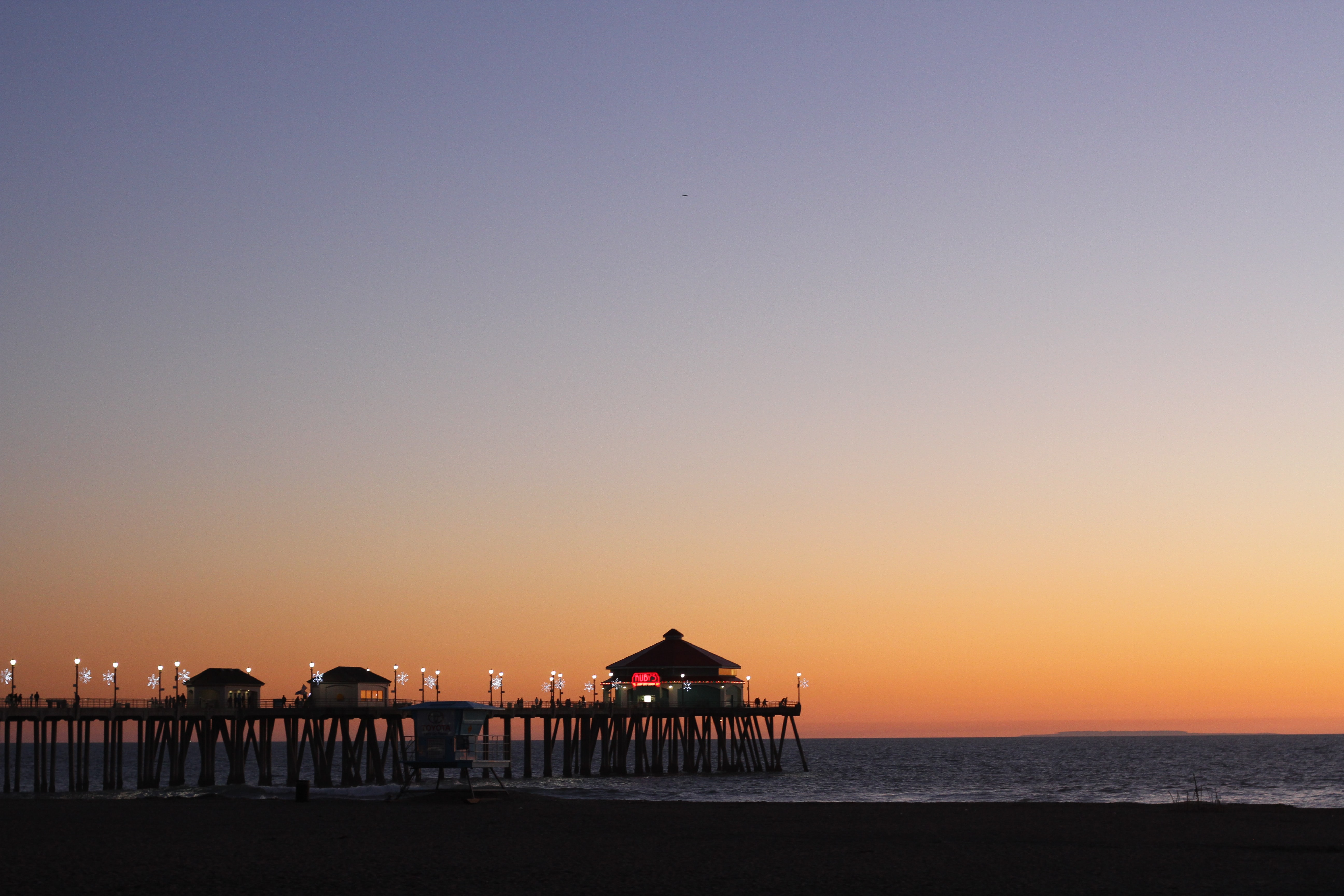 The sun setting behind the twinkling lights of the Huntington Beach pier, California