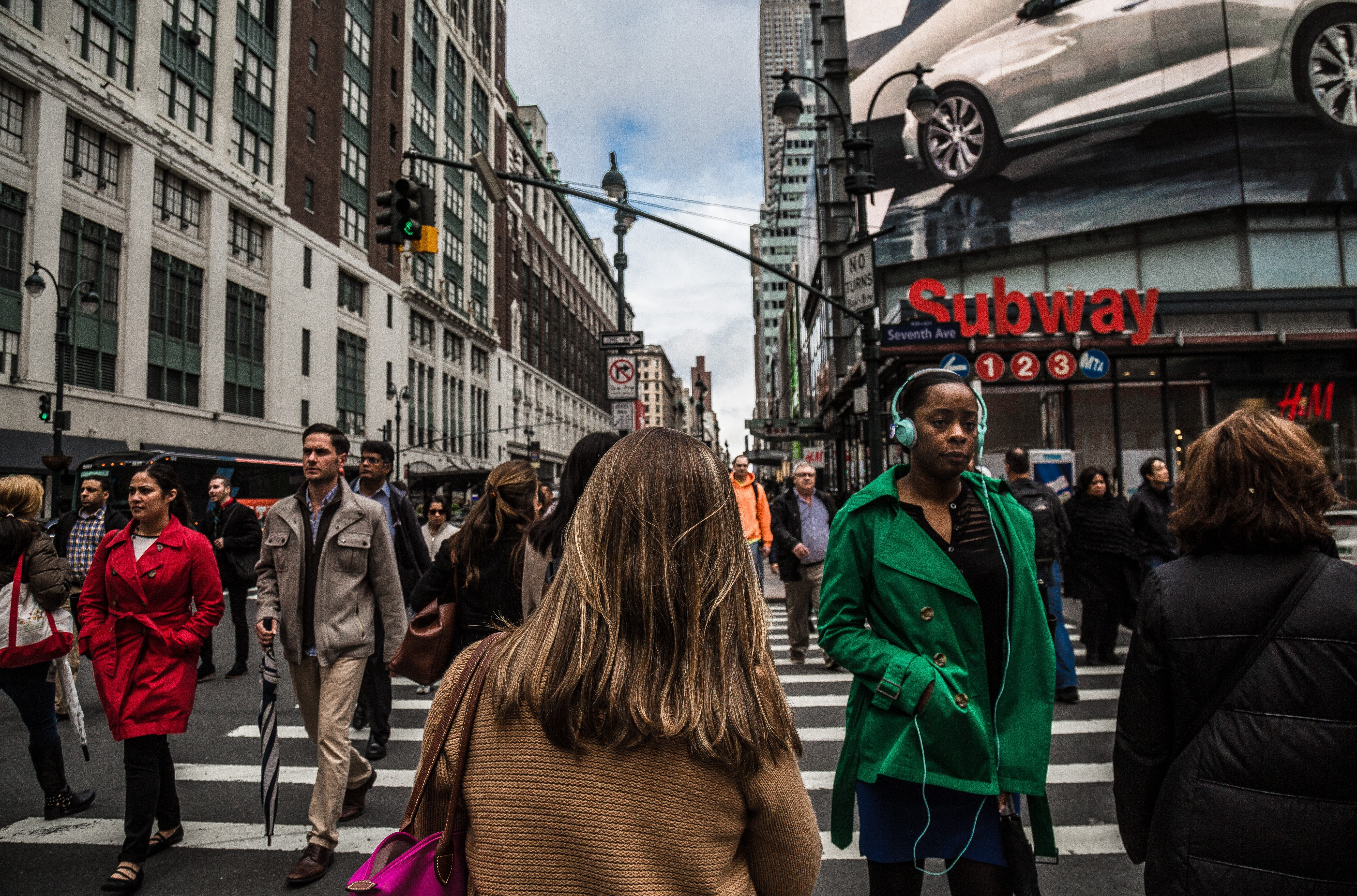 A crowd walks on a New York street among billboards, buildings, and a subway station
