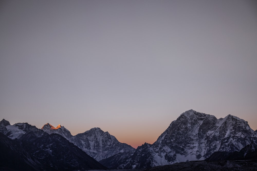 high angle landscape photography of snow covered mountain ranges during golden hour