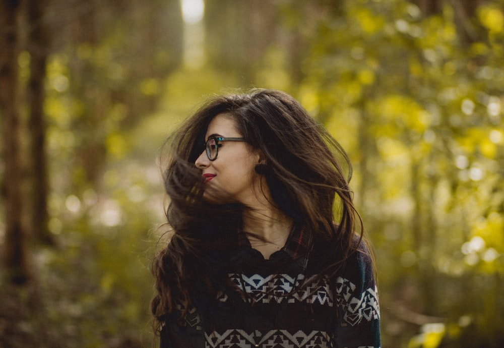 selective focus photography of woman wearing black and white tribal pattern blouse near green trees during daytime