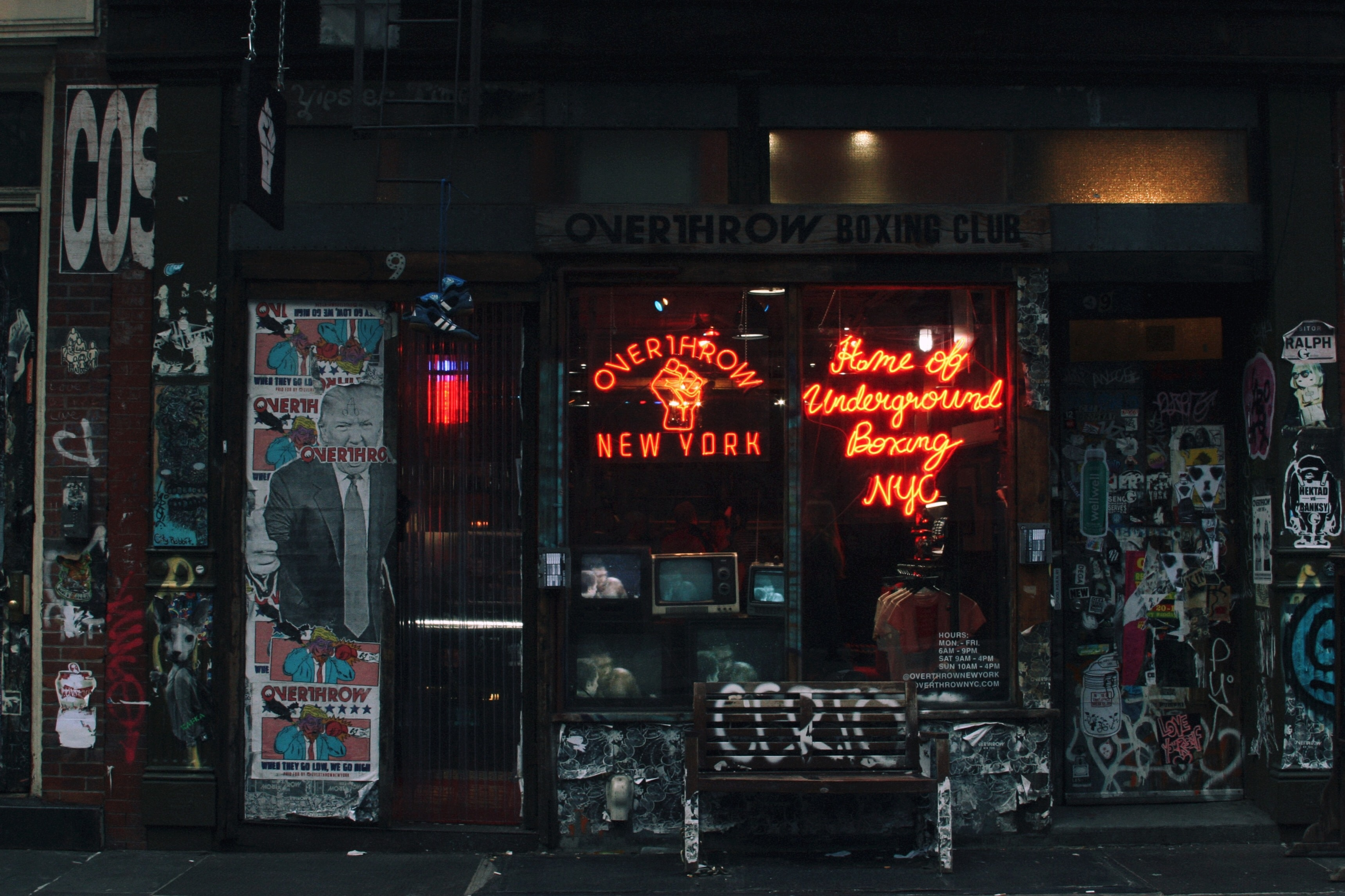 Overthrow boxing club with red neon sign and graffiti covered walls and bench in East Village