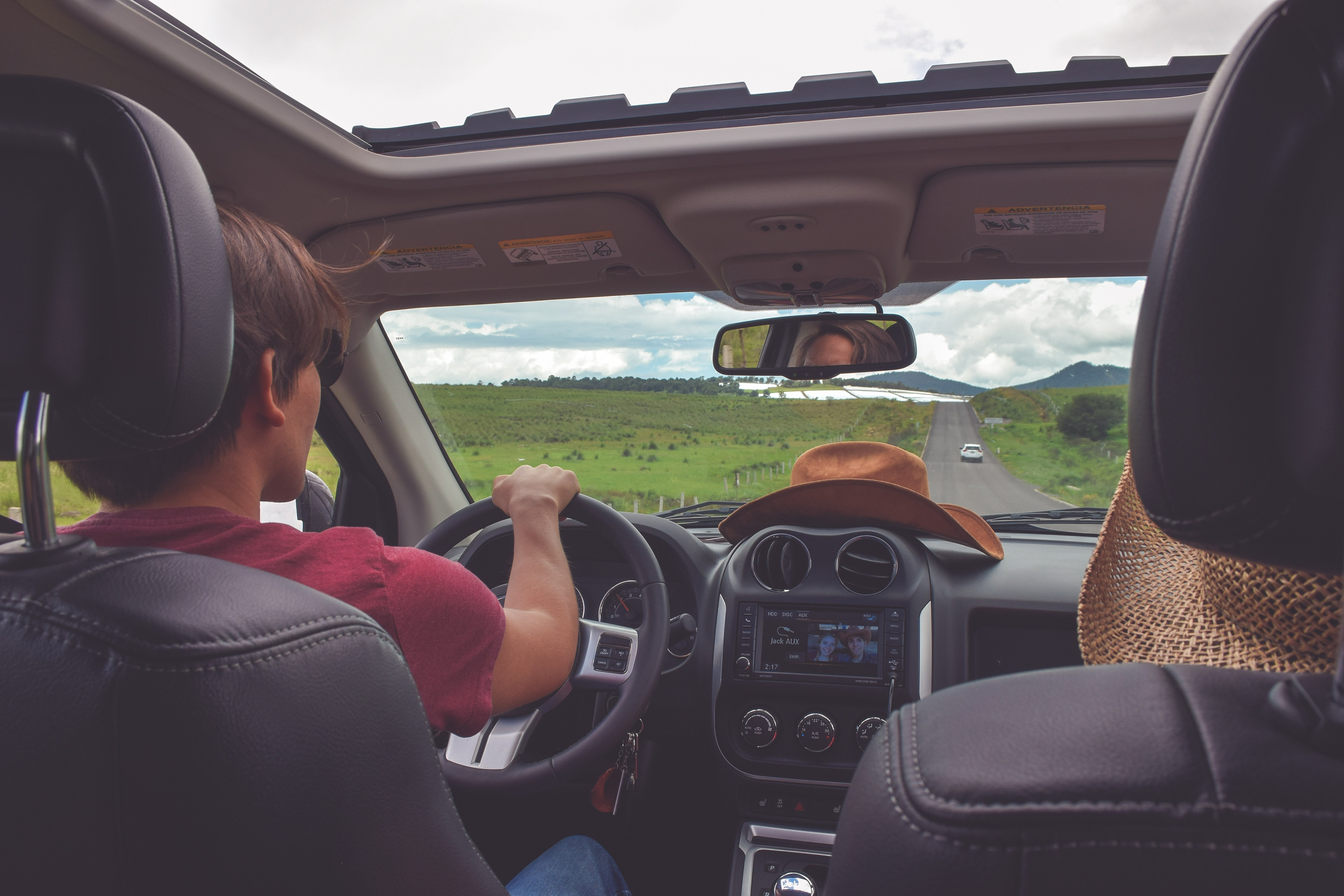 A view from a backseat on the dashboard of a car driven by a young man with rural landscape in front of it