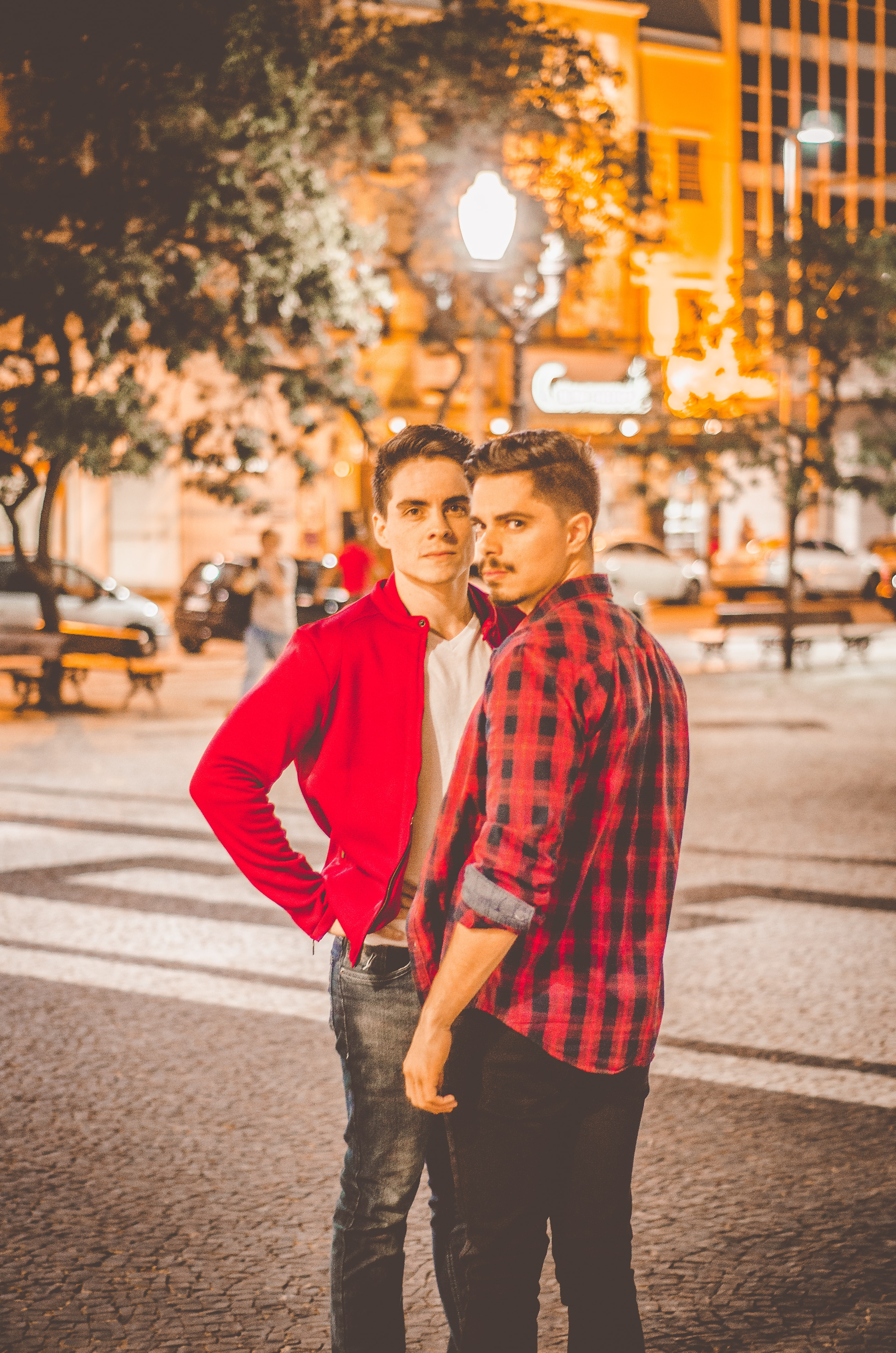 Two young men standing close together at night in a city square