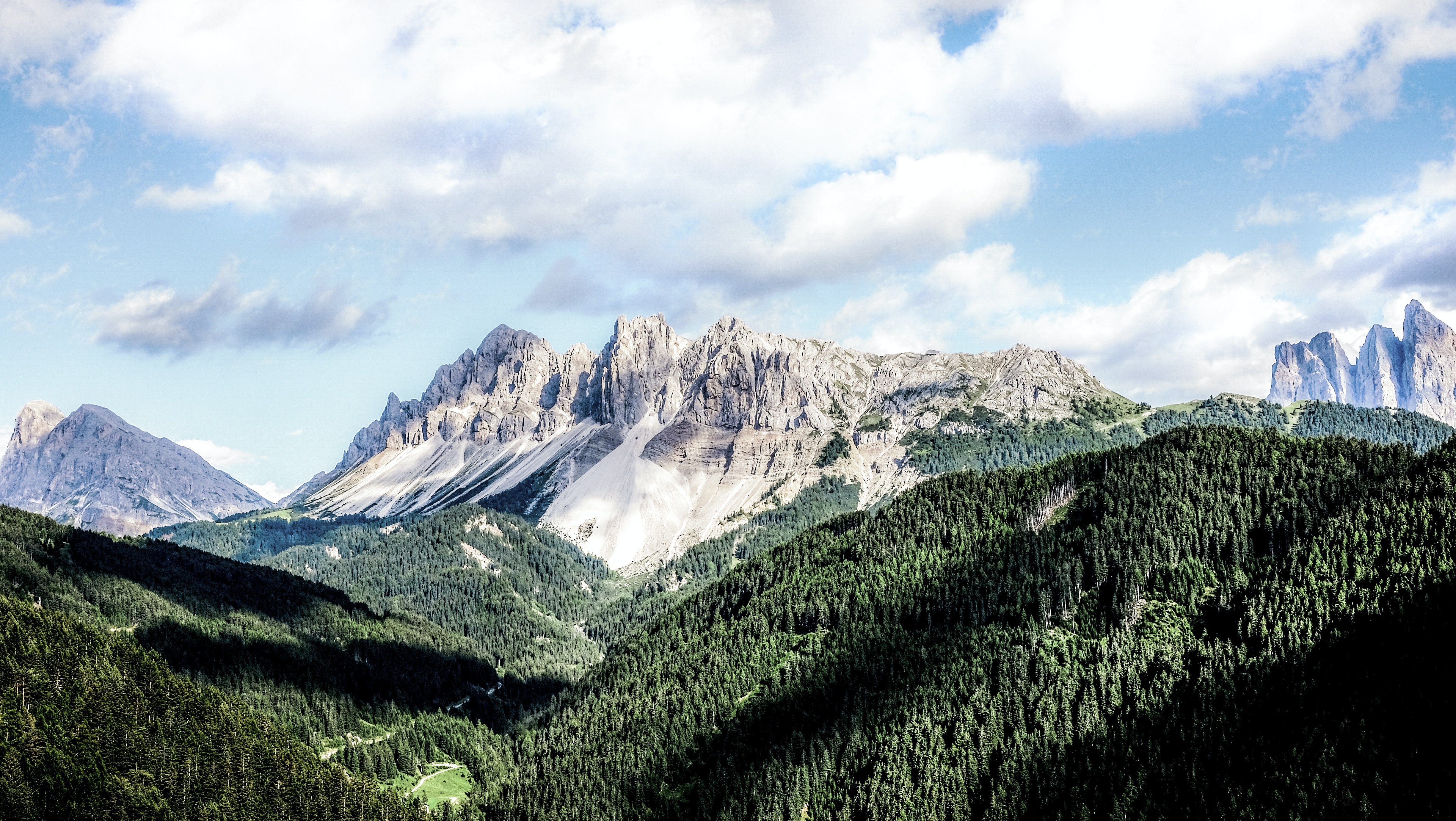 A mountain ridge with jagged peaks towering over a wooded valley in San Martino in Badia