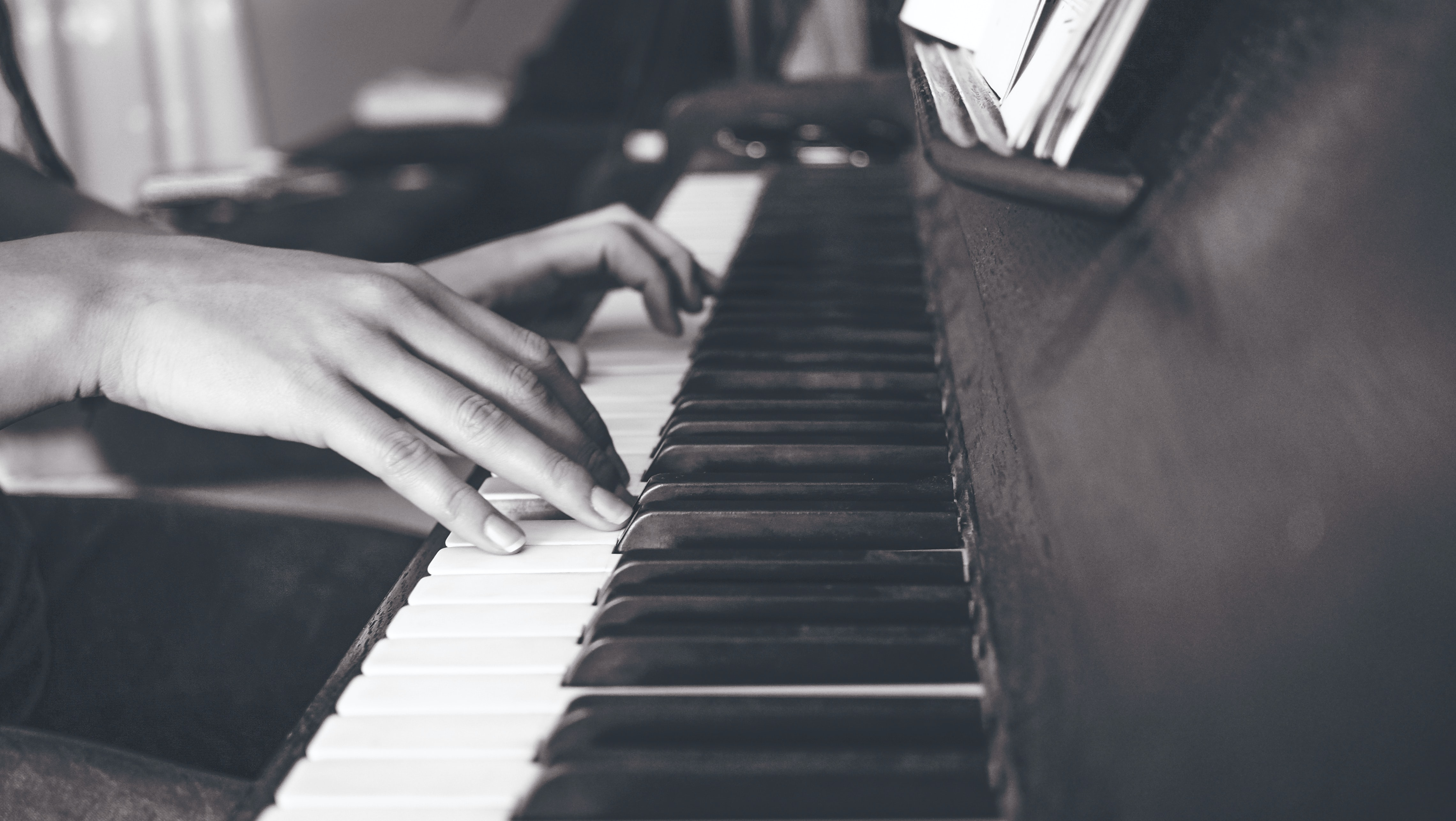 person playing upright piano in sephia photography