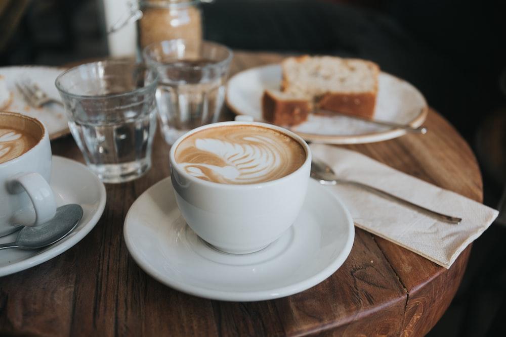 white ceramic mug on white ceramic saucer on brown wooden table
