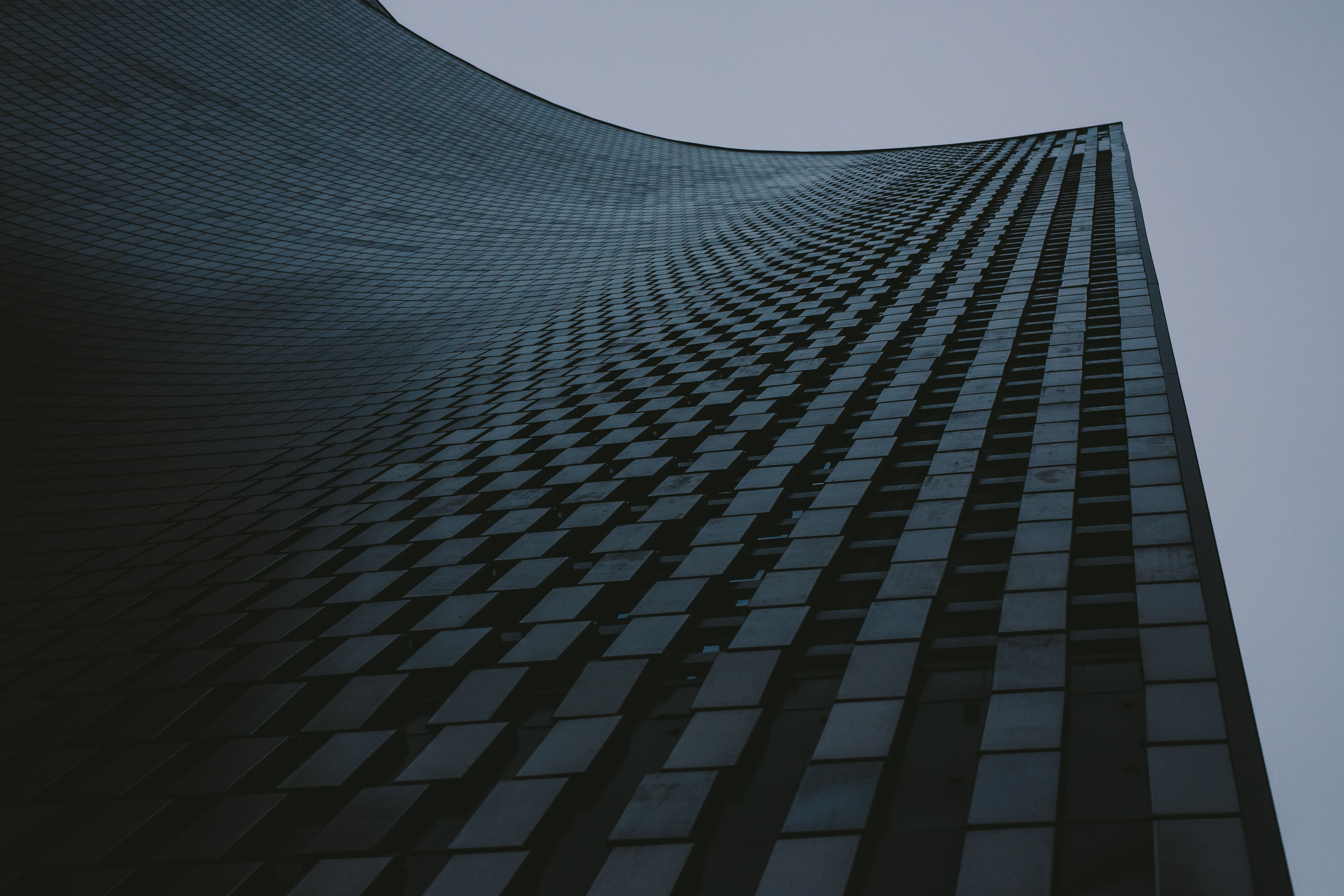 low-angle photography of high-rise building under gray sky